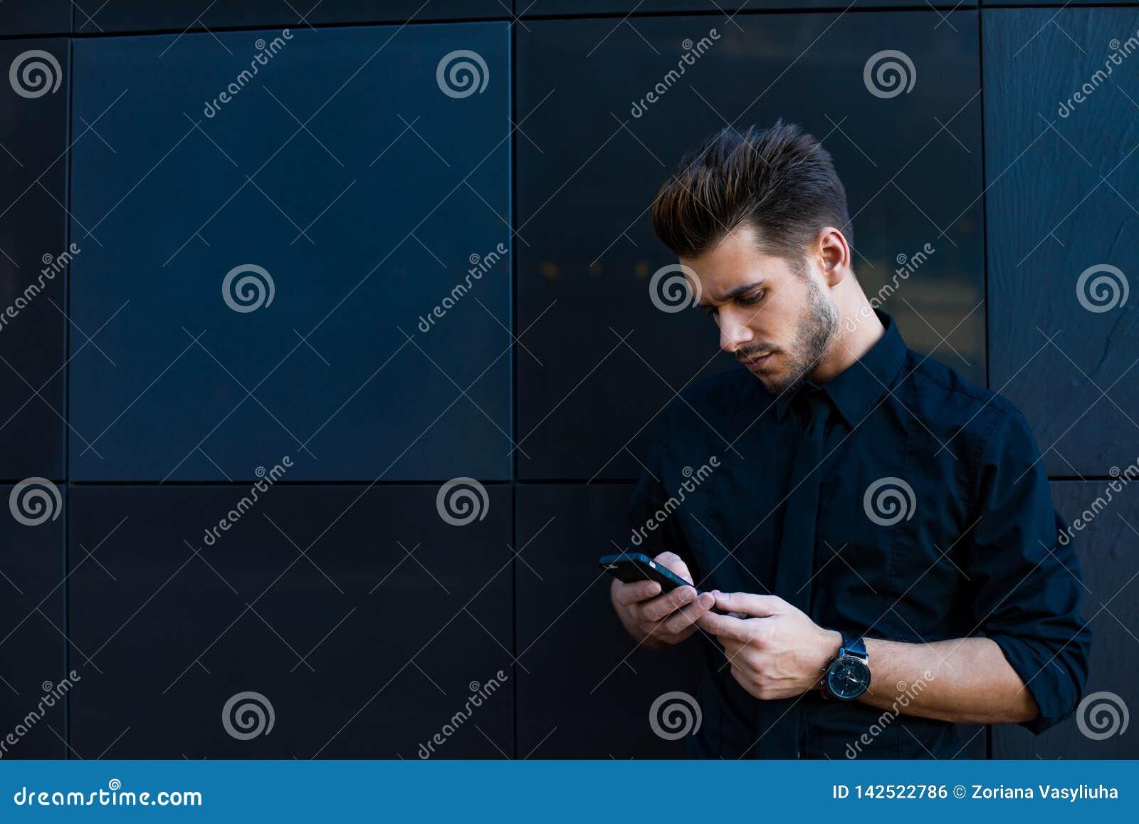 Blije mannelijk hebbend cellphonegesprek tijdens rust in openlucht