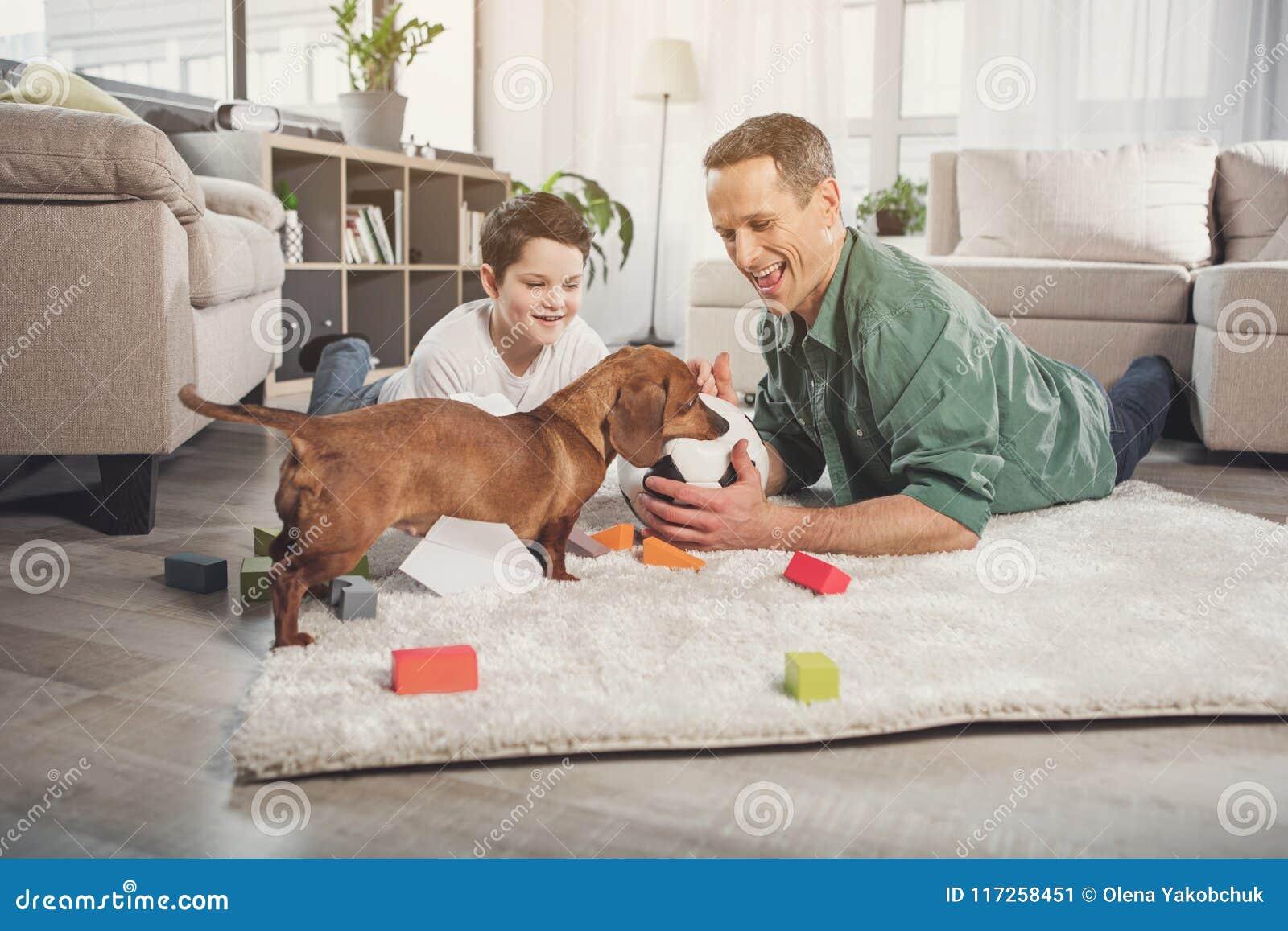 Blije papa en zoons speelvoetbal met puppy