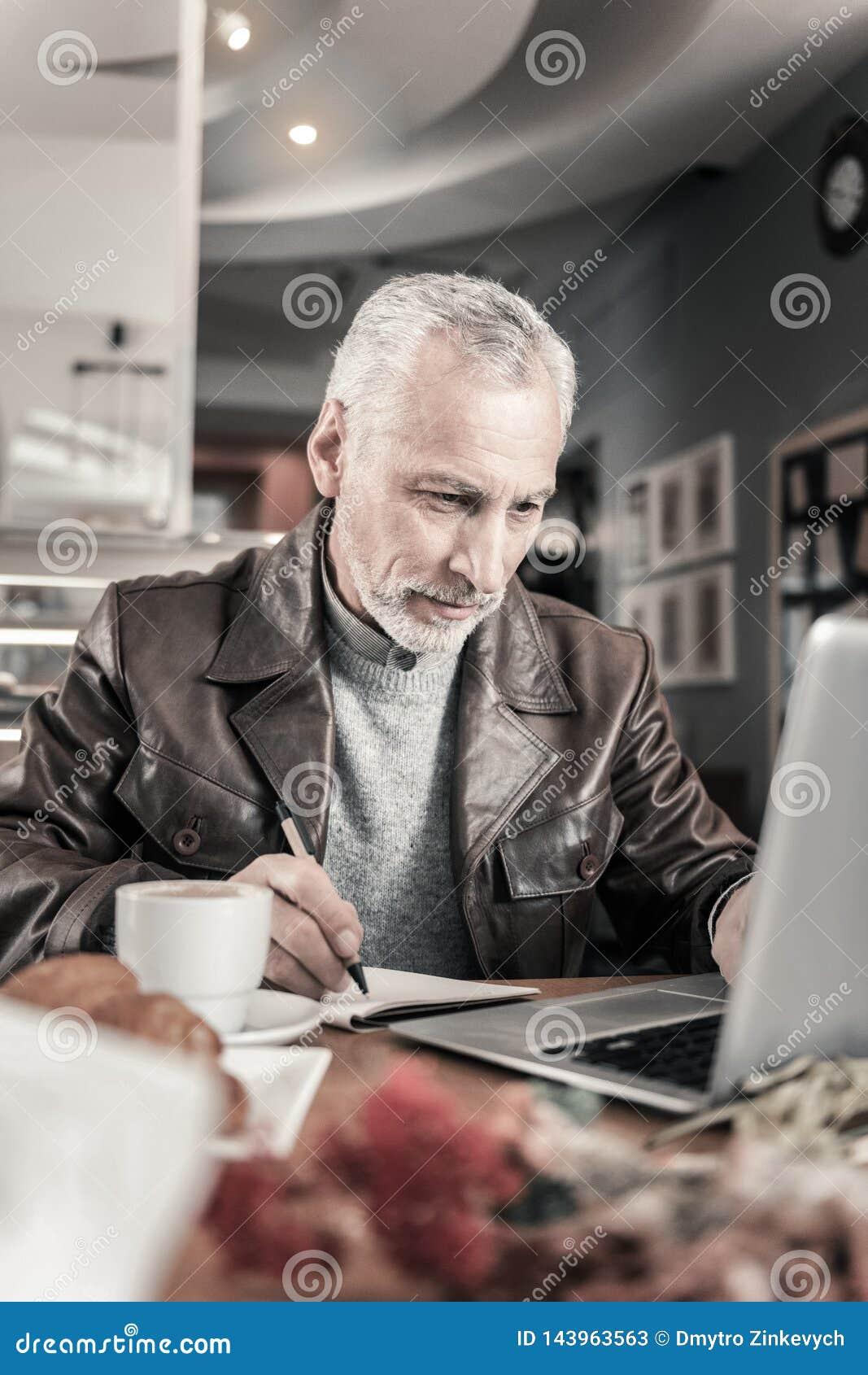 Blije rijpe mens die aan afstand bij computer werken
