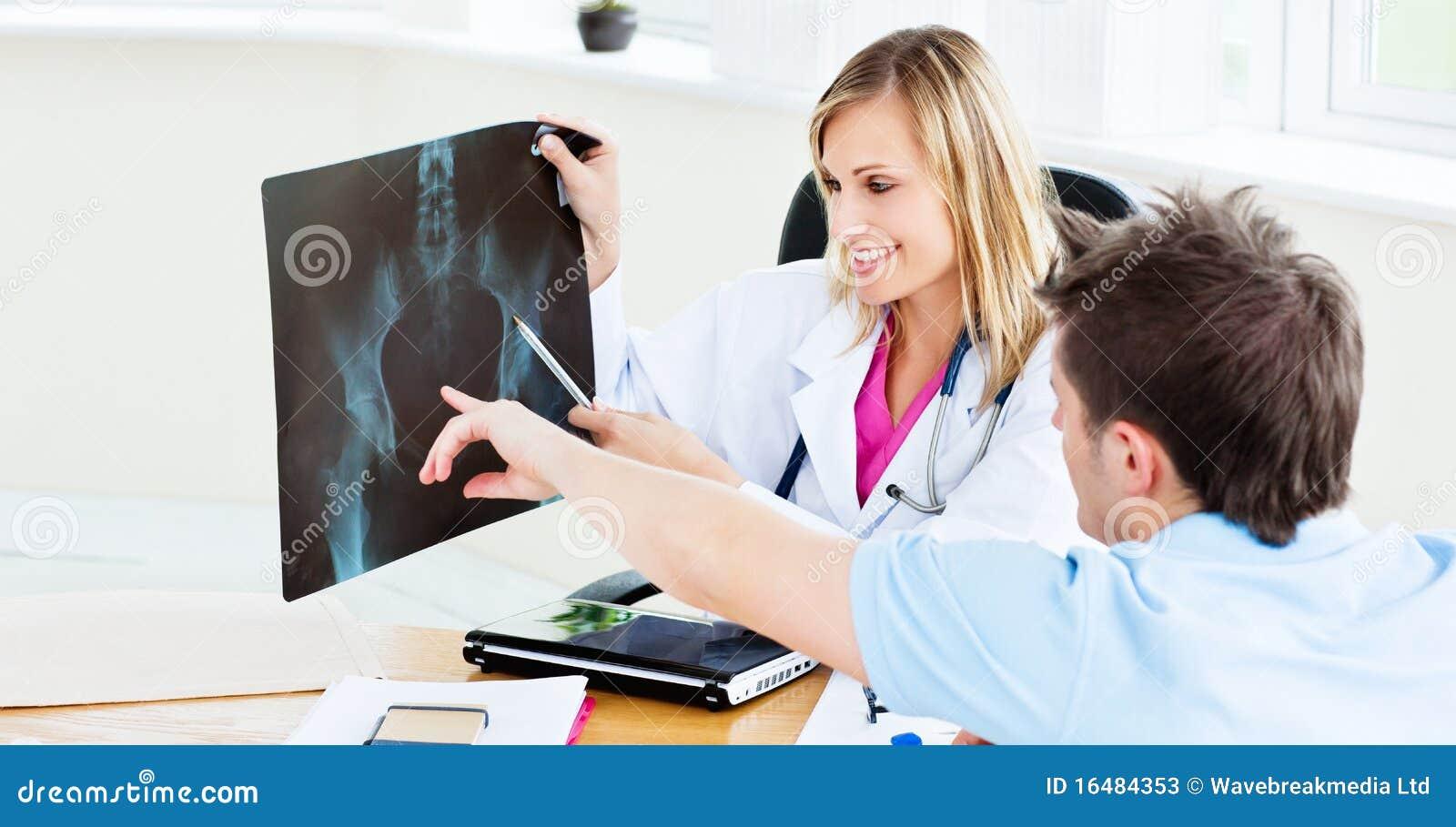 Blije vrouwelijke arts die een röntgenstraal toont aan een patiënt