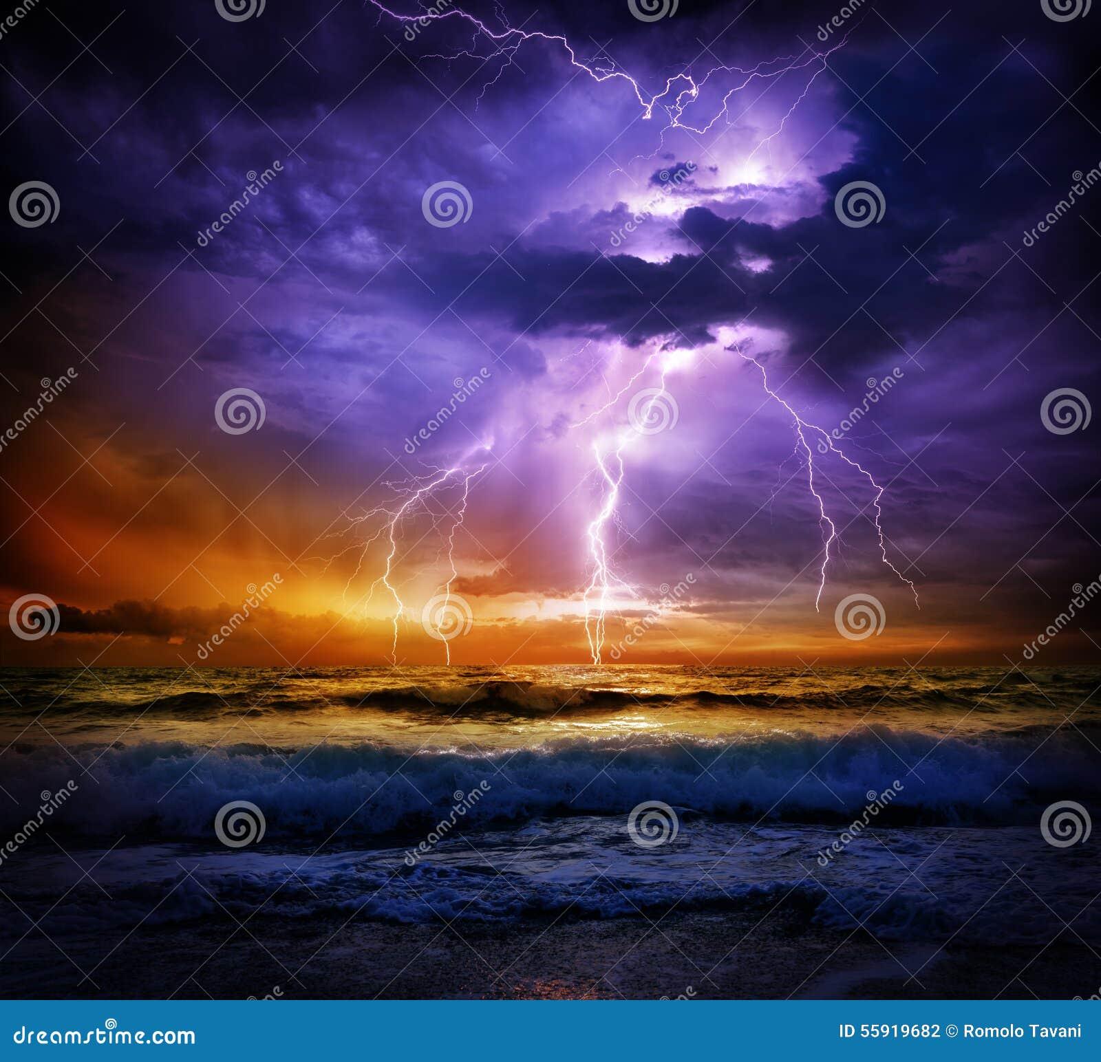 Bliksem en onweer op overzees aan de zonsondergang