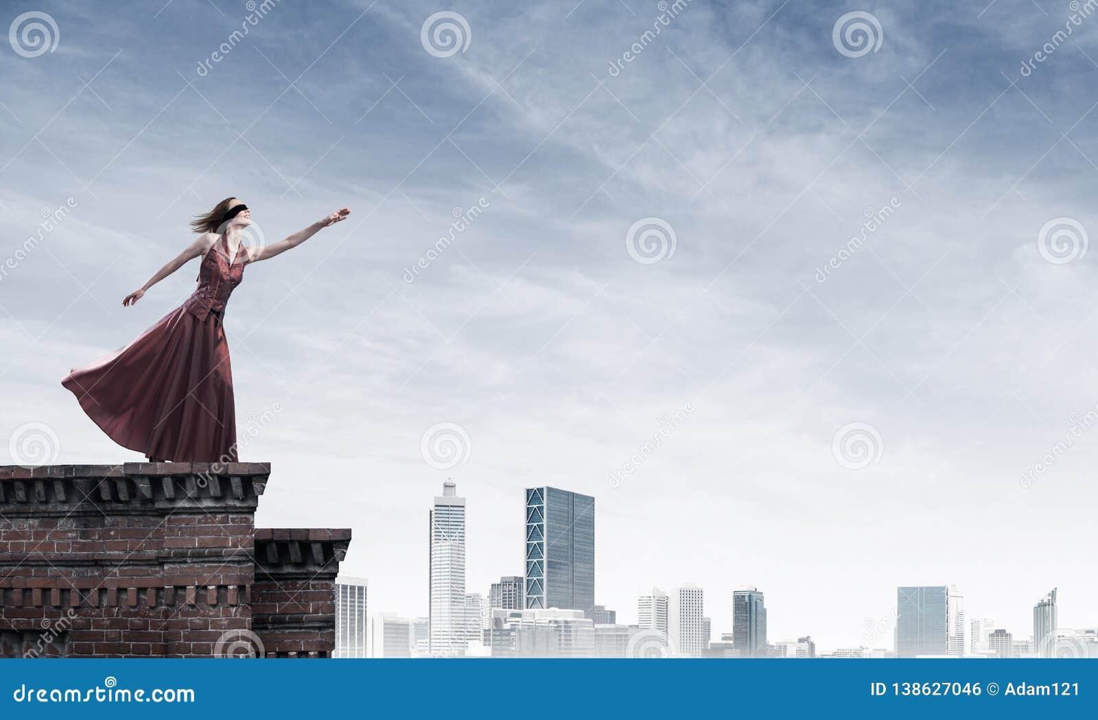 Blind kvinna i lång röd klänning överst av byggnad Blandat massmedia