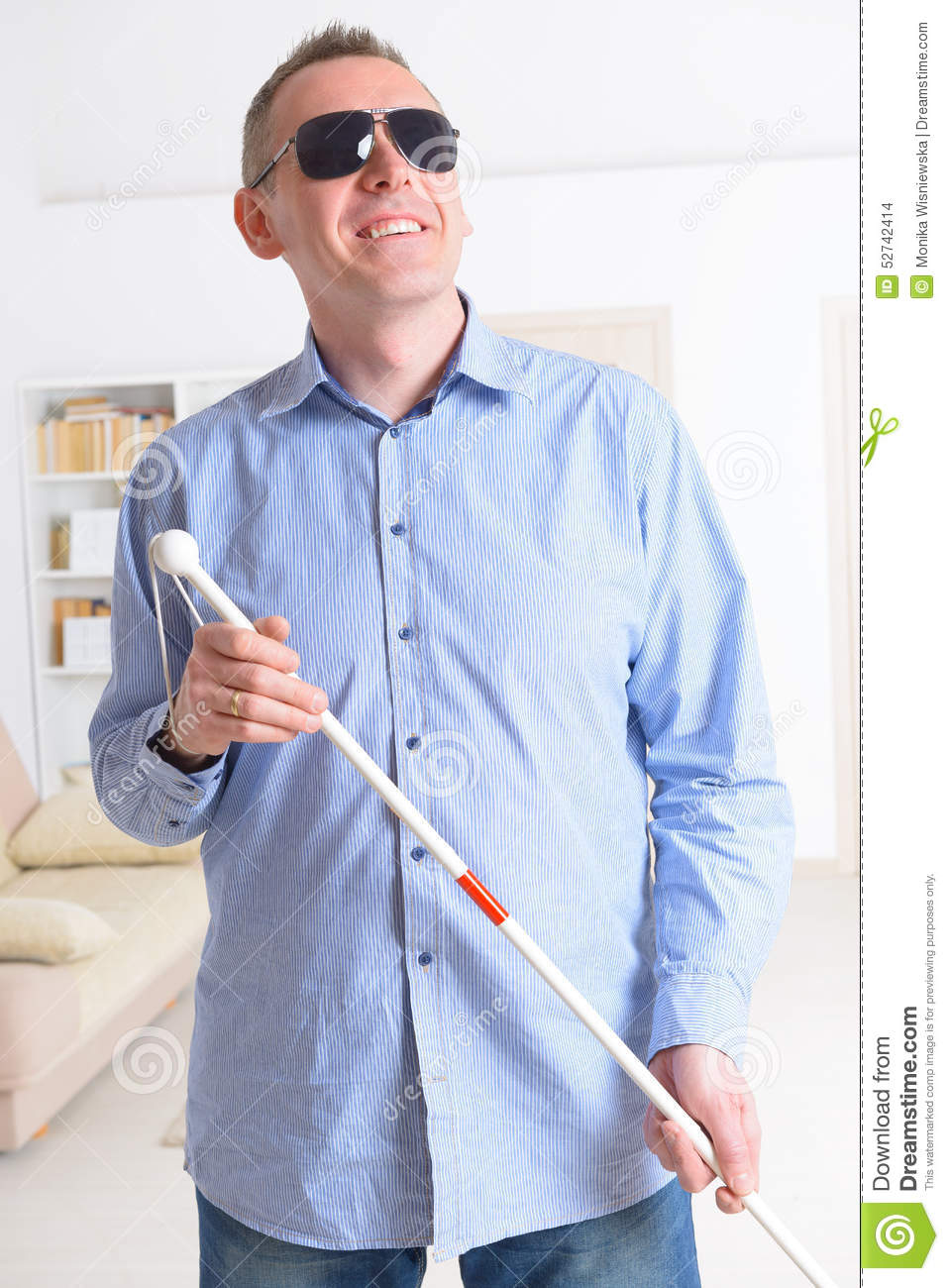 Blind man with white stick and dark glasses at home.