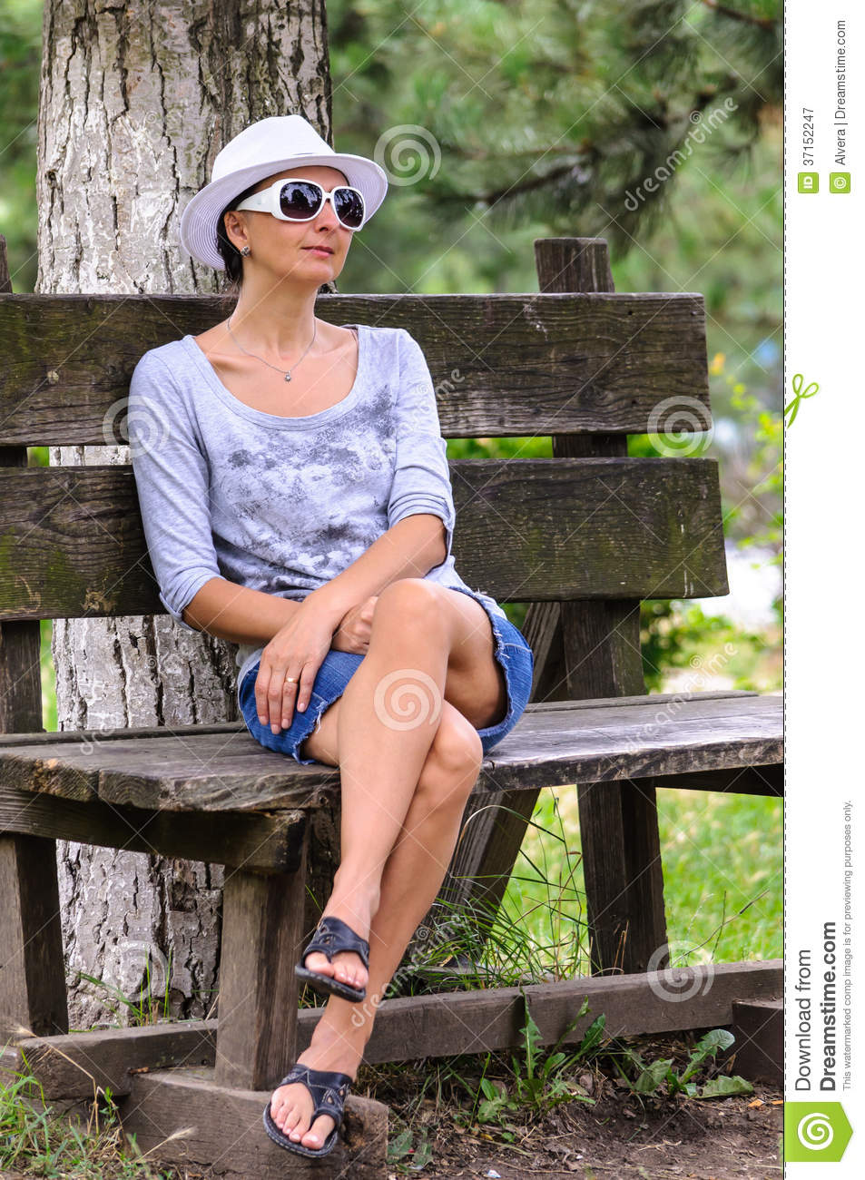 Blind woman resting, sitting on old wooden bench in park. White hat ...