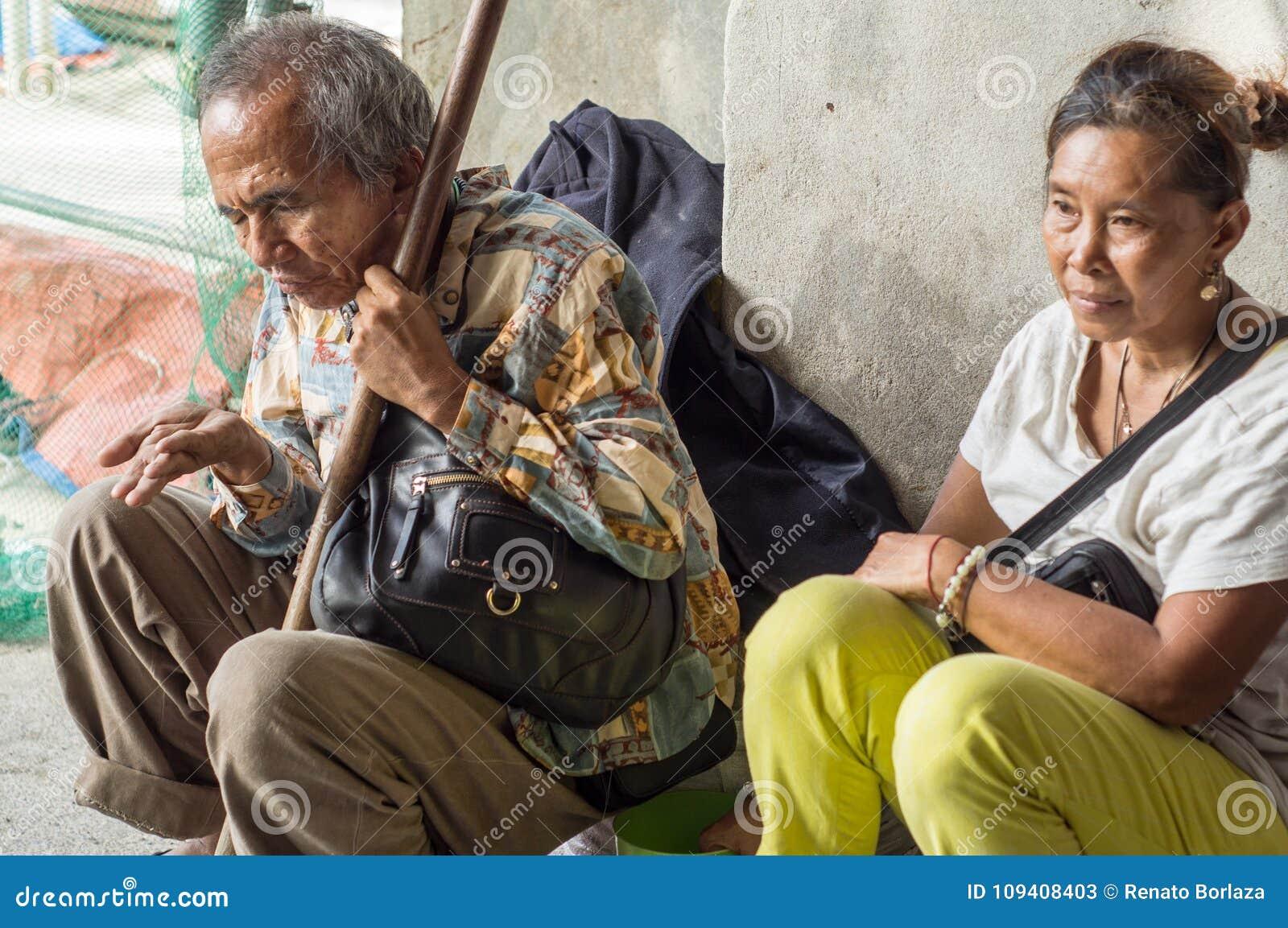 Blinde oude mannelijke bedelaar en vrouwenescorte die aalmoes zoeken bij kerk poortruïnes