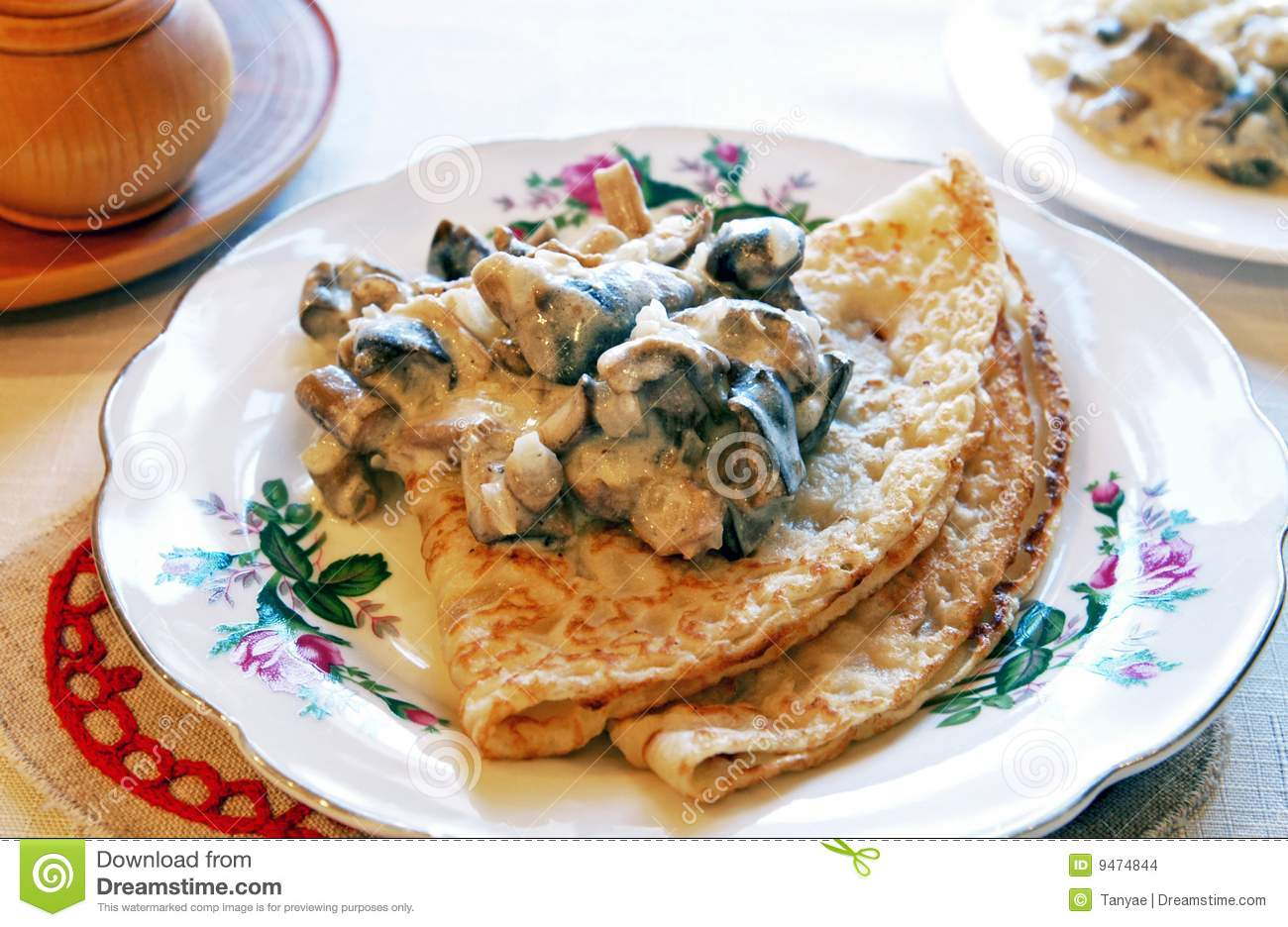 Blini with mushrooms in white sauce