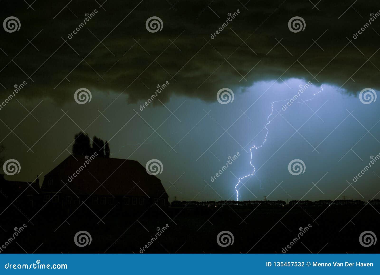 Blixtslag på ett mörkt - blå himmel över en huskontur