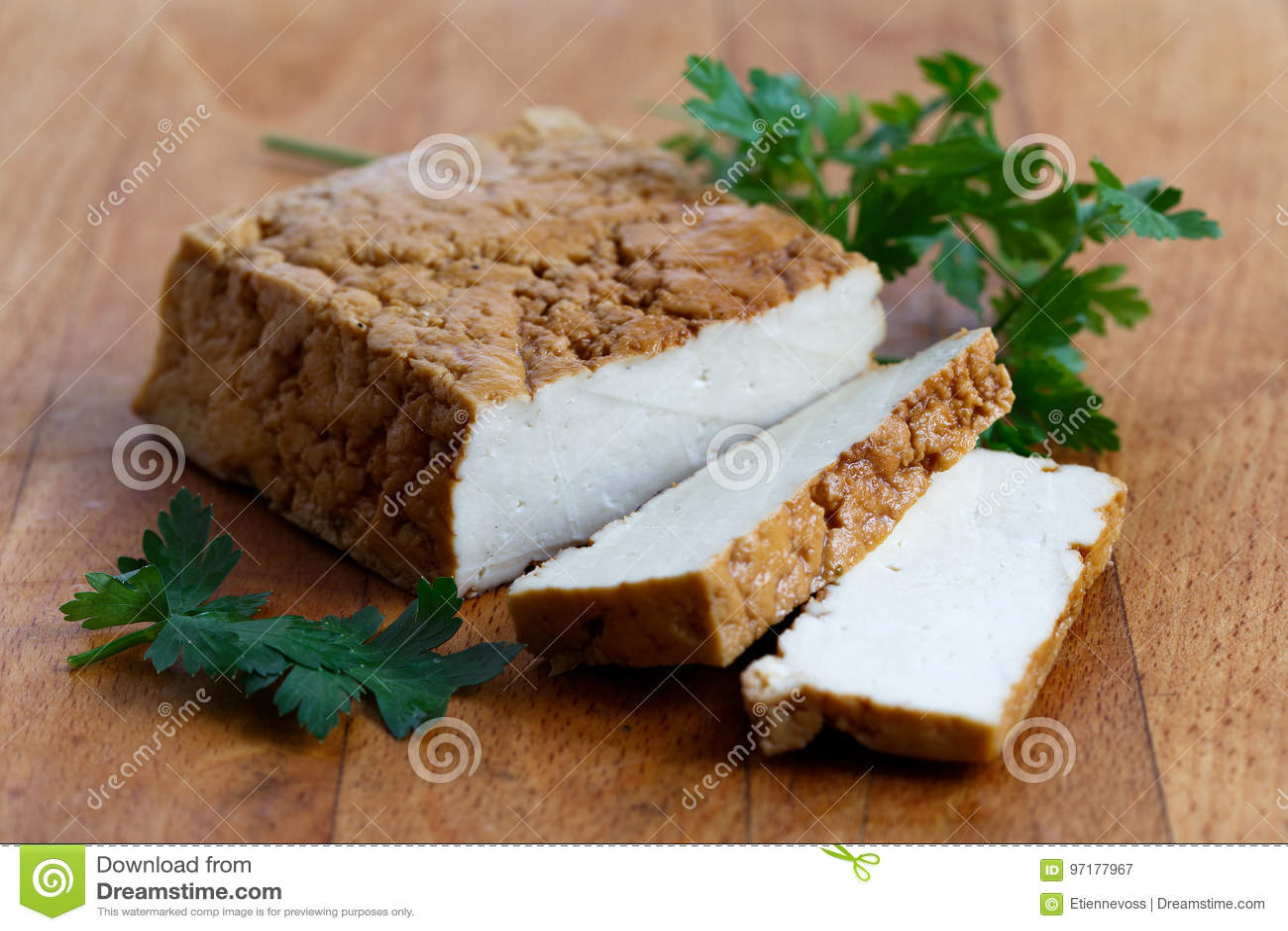 Bloc de tofu fumé, de deux tranches de tofu et de persil frais sur le bois