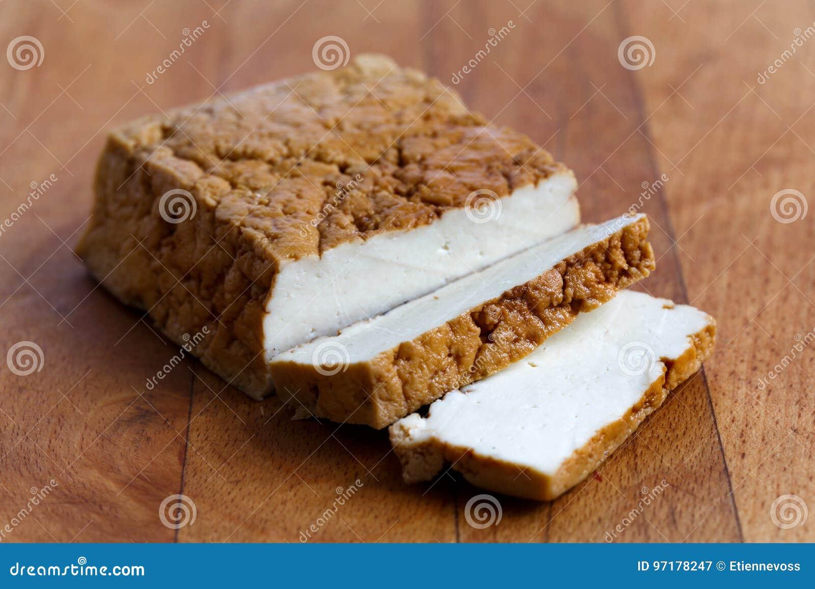 Bloc de tofu fumé et de deux tranches de tofu sur le verrat de hachage en bois