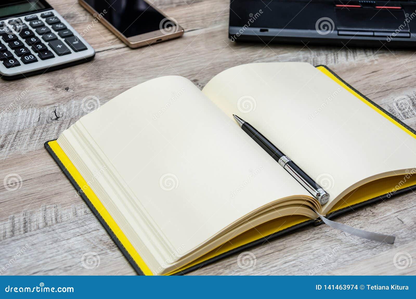 Bloc-notes, stylo, smartphone et partie de l ordinateur portable sur un fond en bois