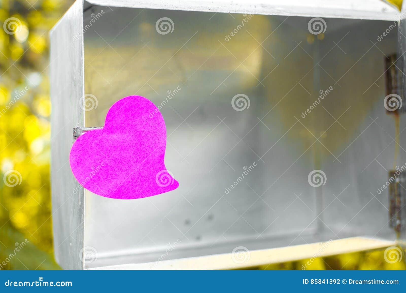 Blocco note in bianco o rosa appiccicoso delle note sul contenitore di posta con le sedere di luce solare