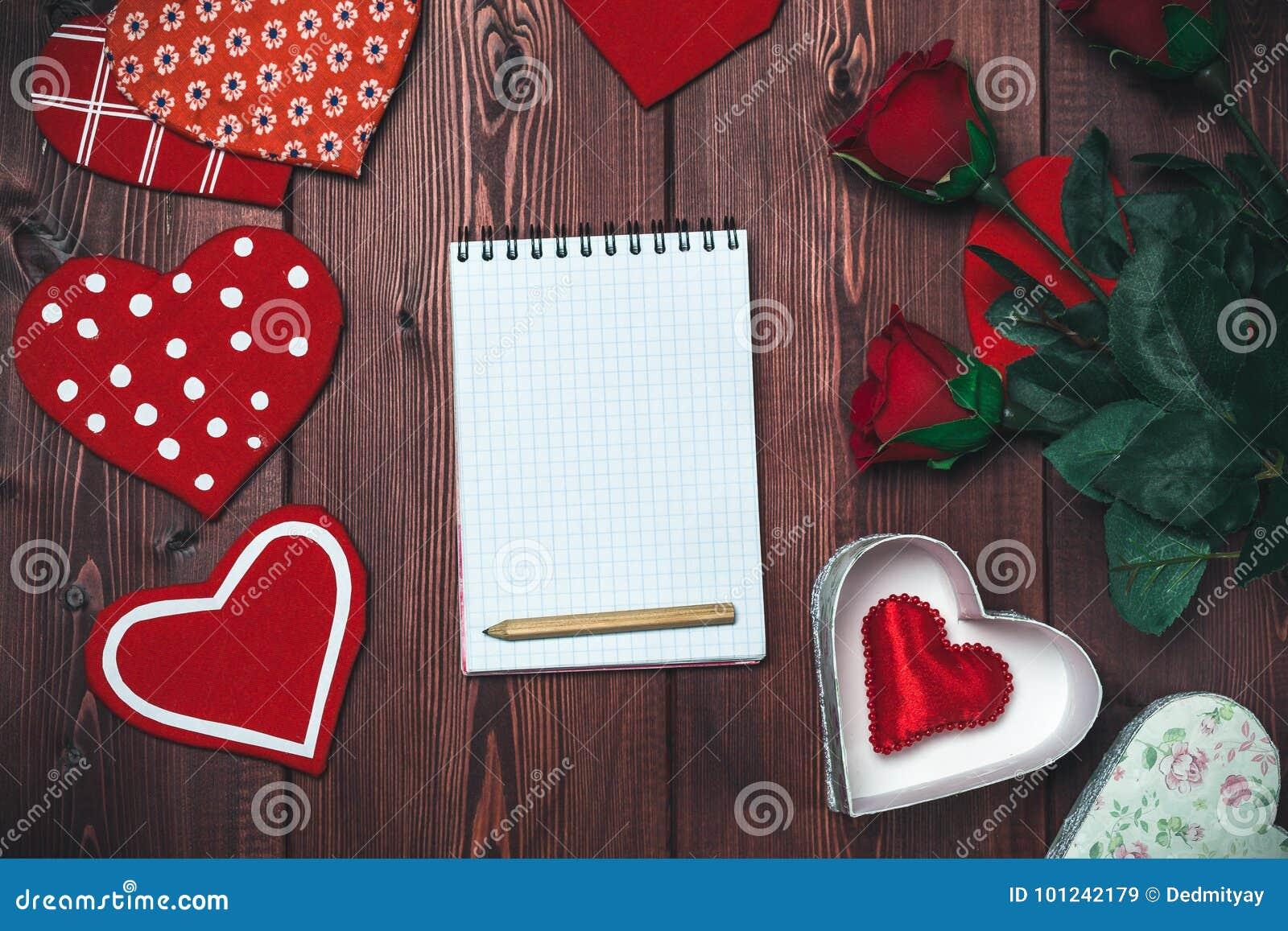Blocco note, cuori del giocattolo e rose rosse alti falsi aperti sulla tavola di legno romantico