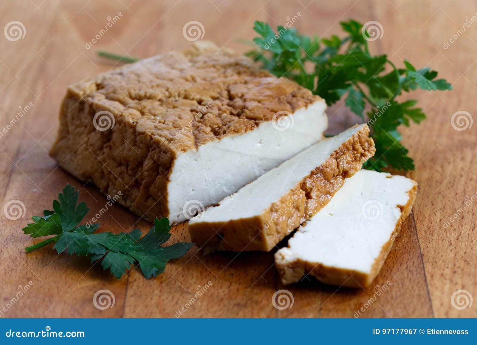 Block of smoked tofu, two tofu slices and fresh parsley on wood