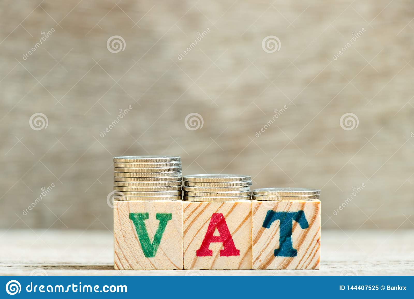 Block in word VAT Value added tax with coin in down trend on wood background
