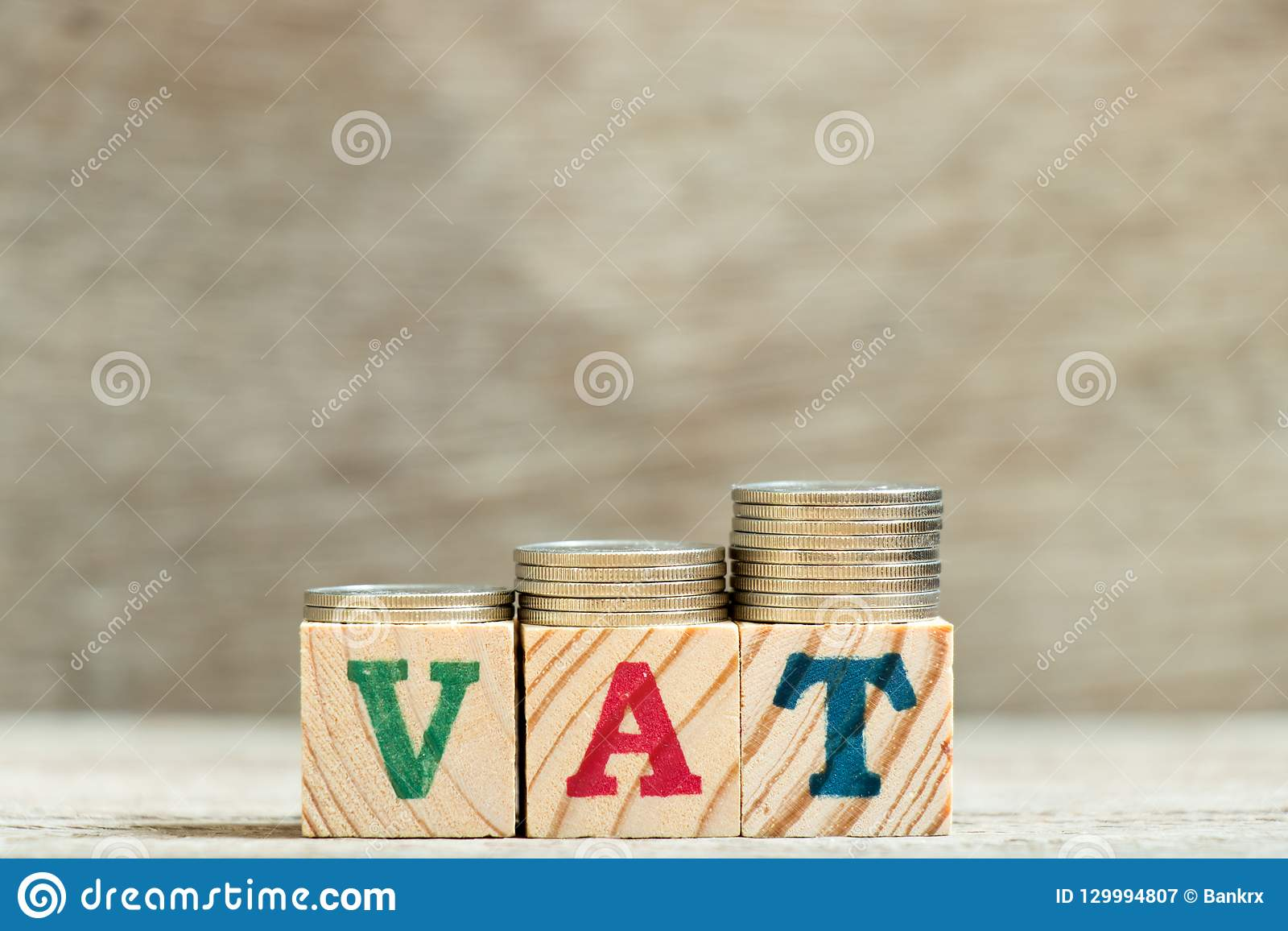 Block in word VAT (Abbreviation of Value added tax) with coin