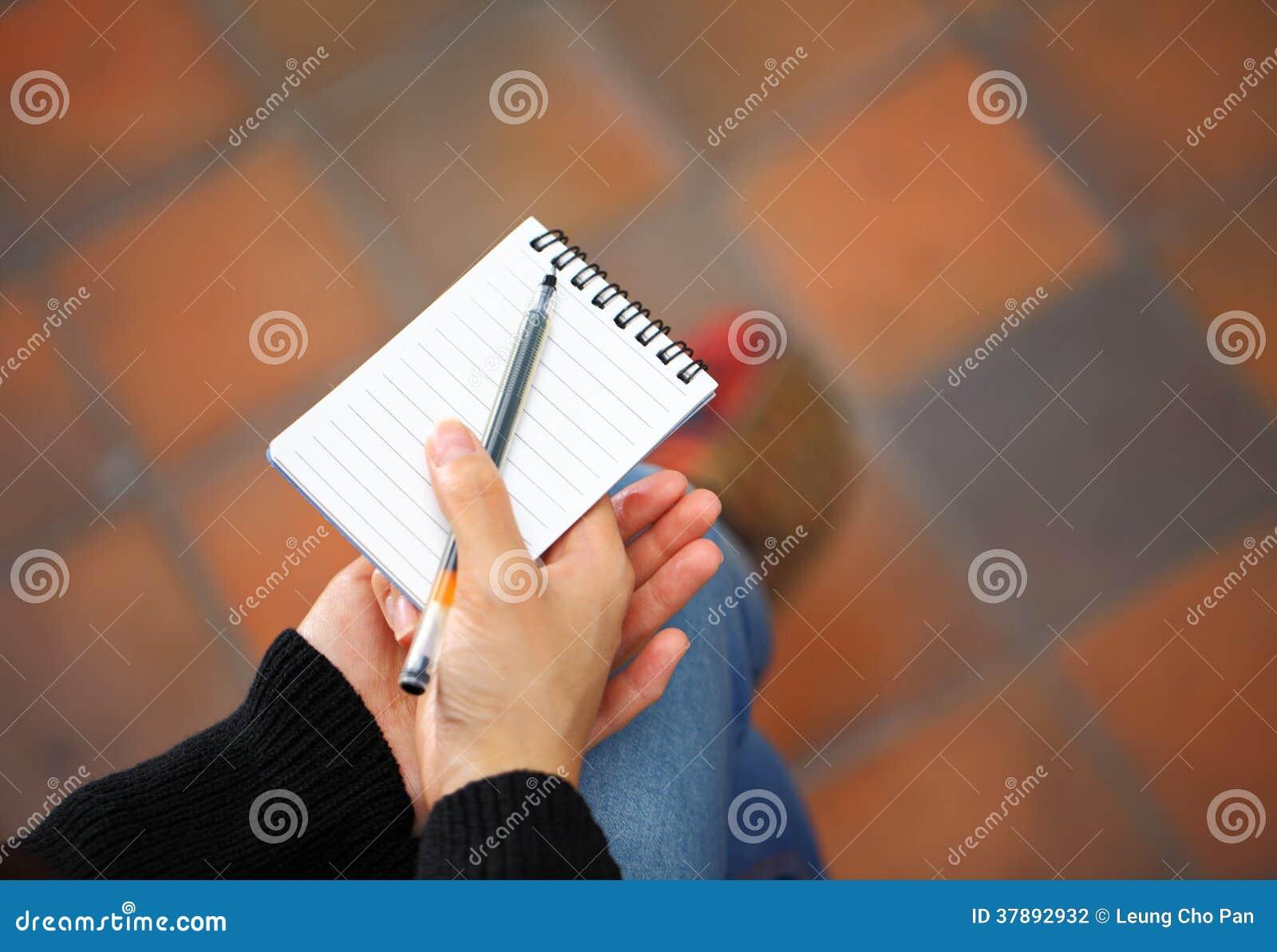 Blocnote en pengreep door vrouwenhand