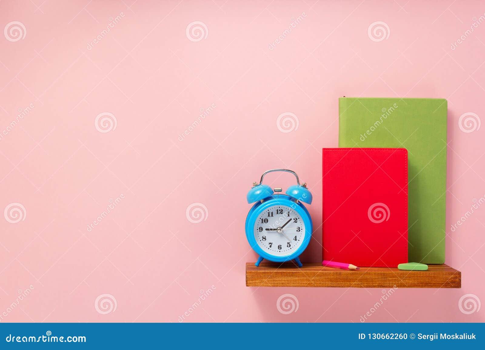 Blocnote en wekker op plank bij muurachtergrond