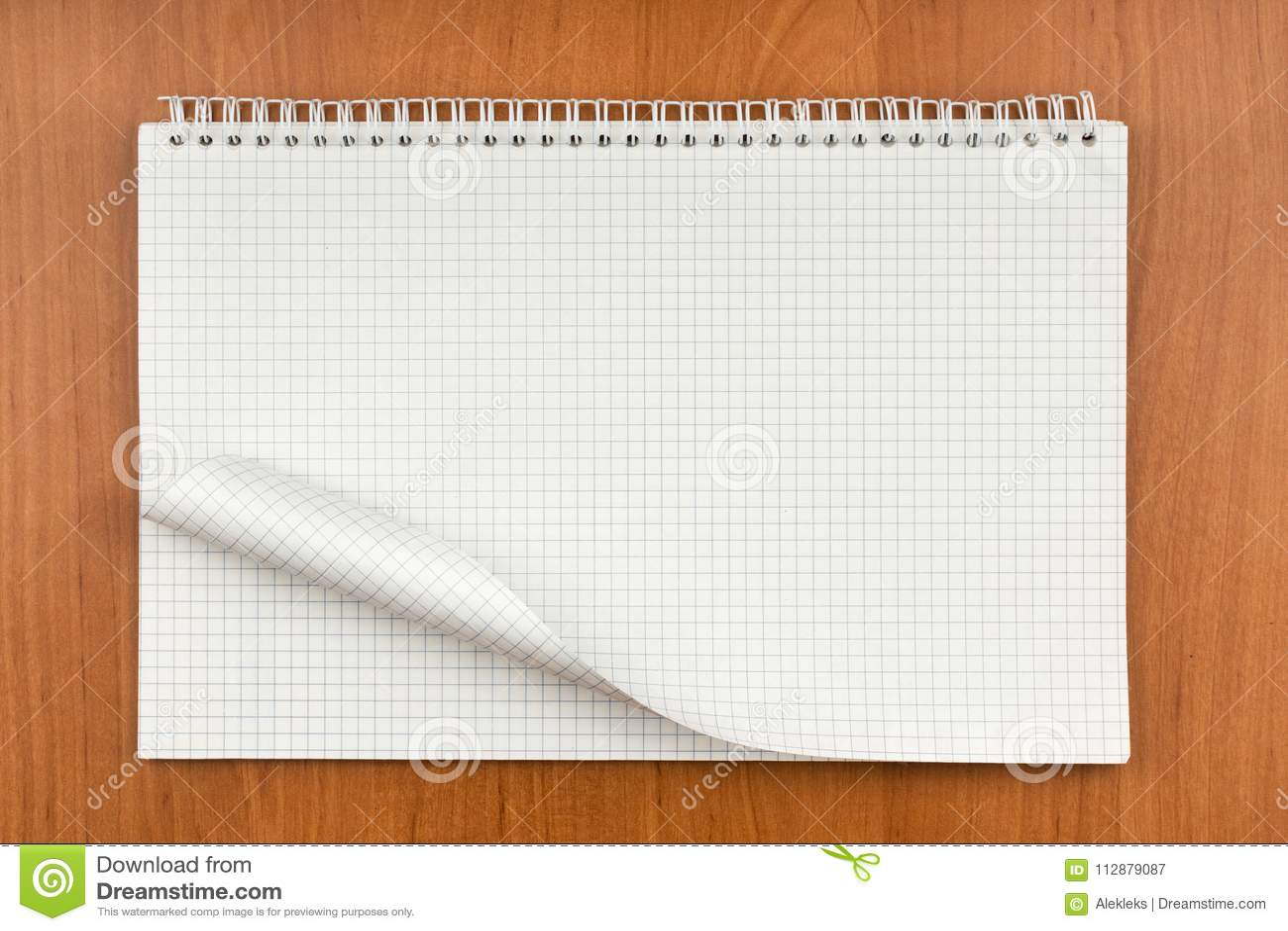 Blocnote op een spiraal met een gekruld blad die op een lijst liggen