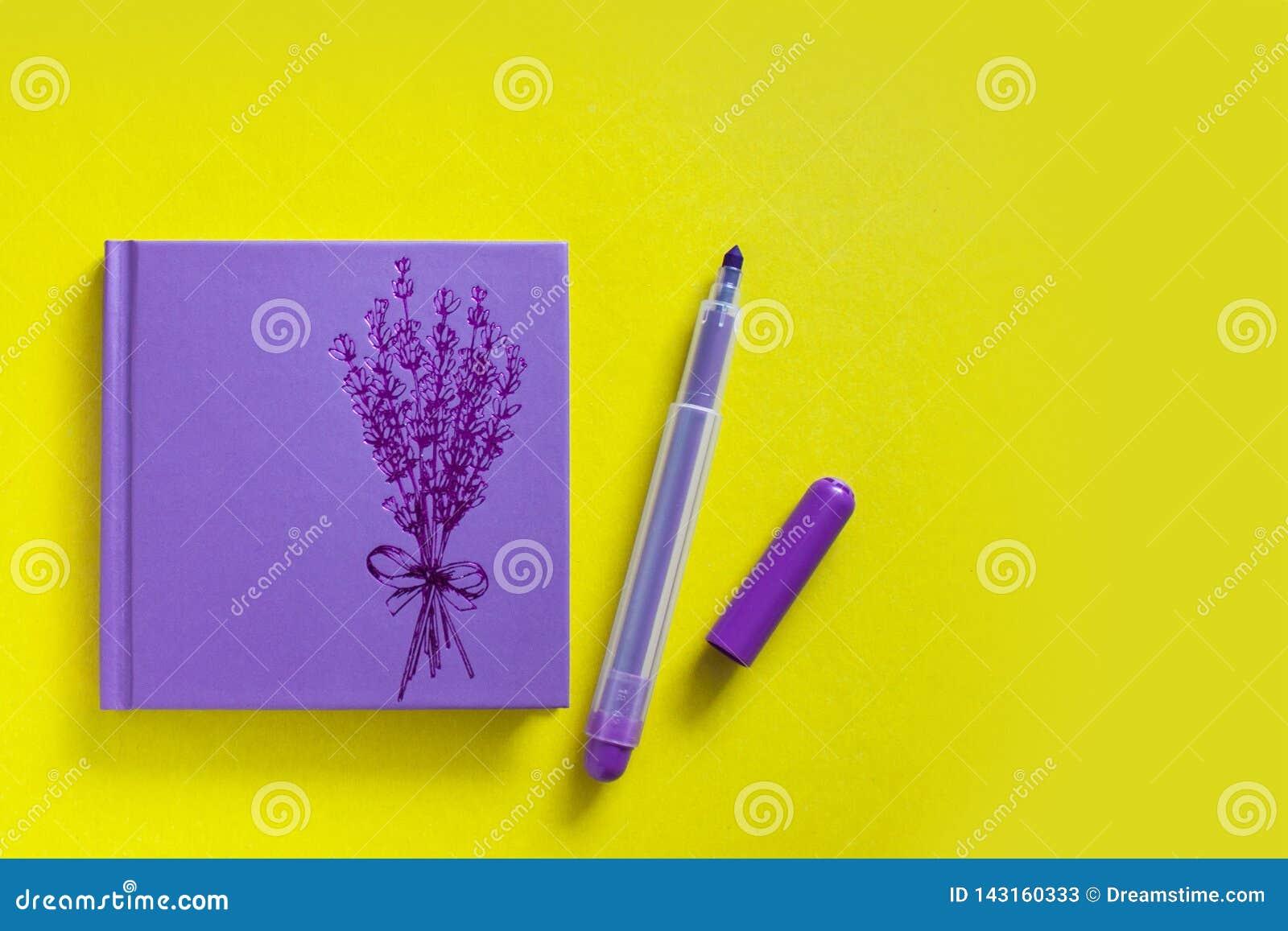 Bloco de notas lilás com a pena de feltro no fundo amarelo