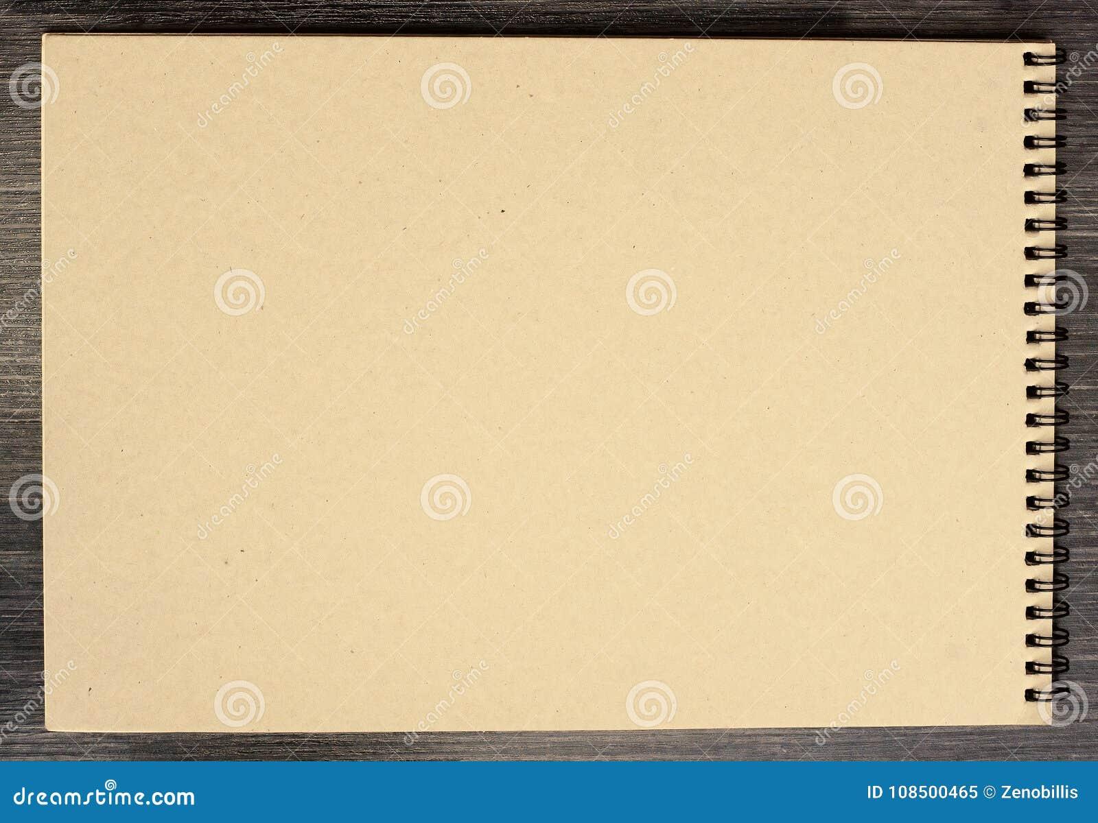 Bloco de notas vazio para esboçar com as páginas amareladas do cartão no fundo preto
