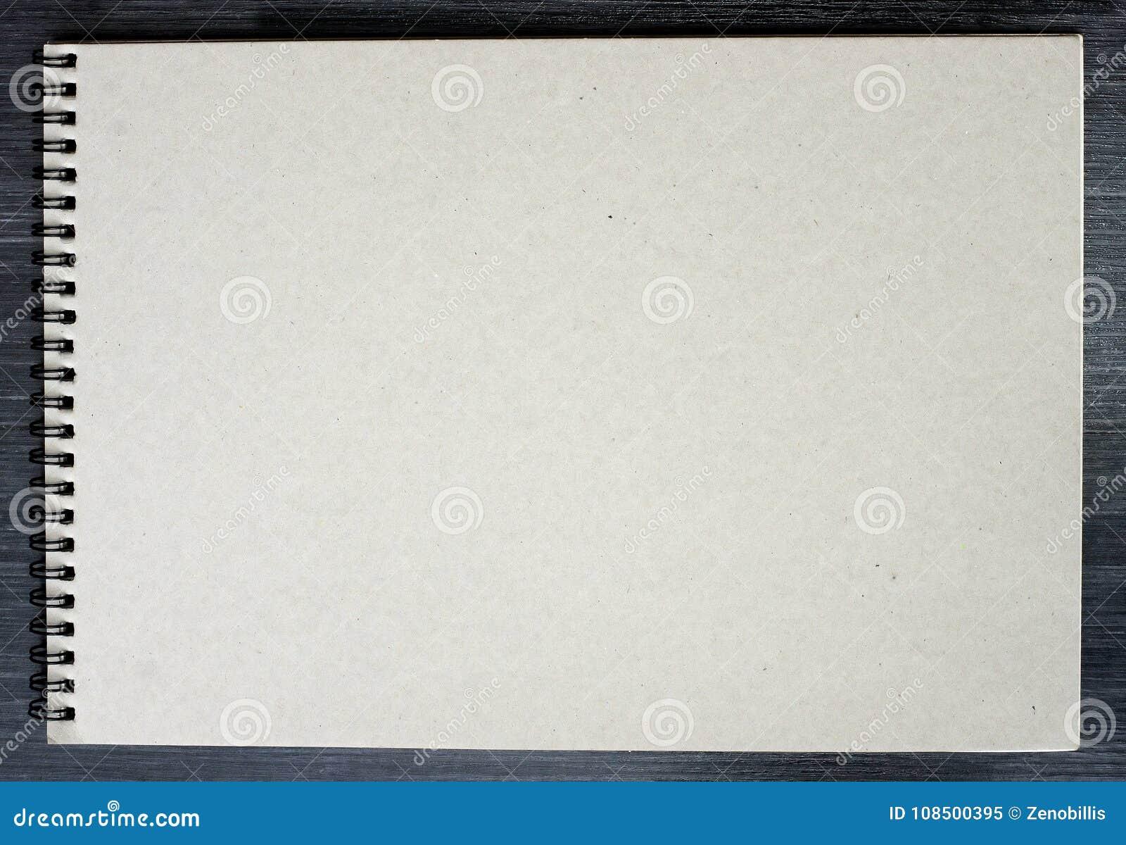 Bloco de notas vazio para esboçar com as páginas do cartão no fundo preto