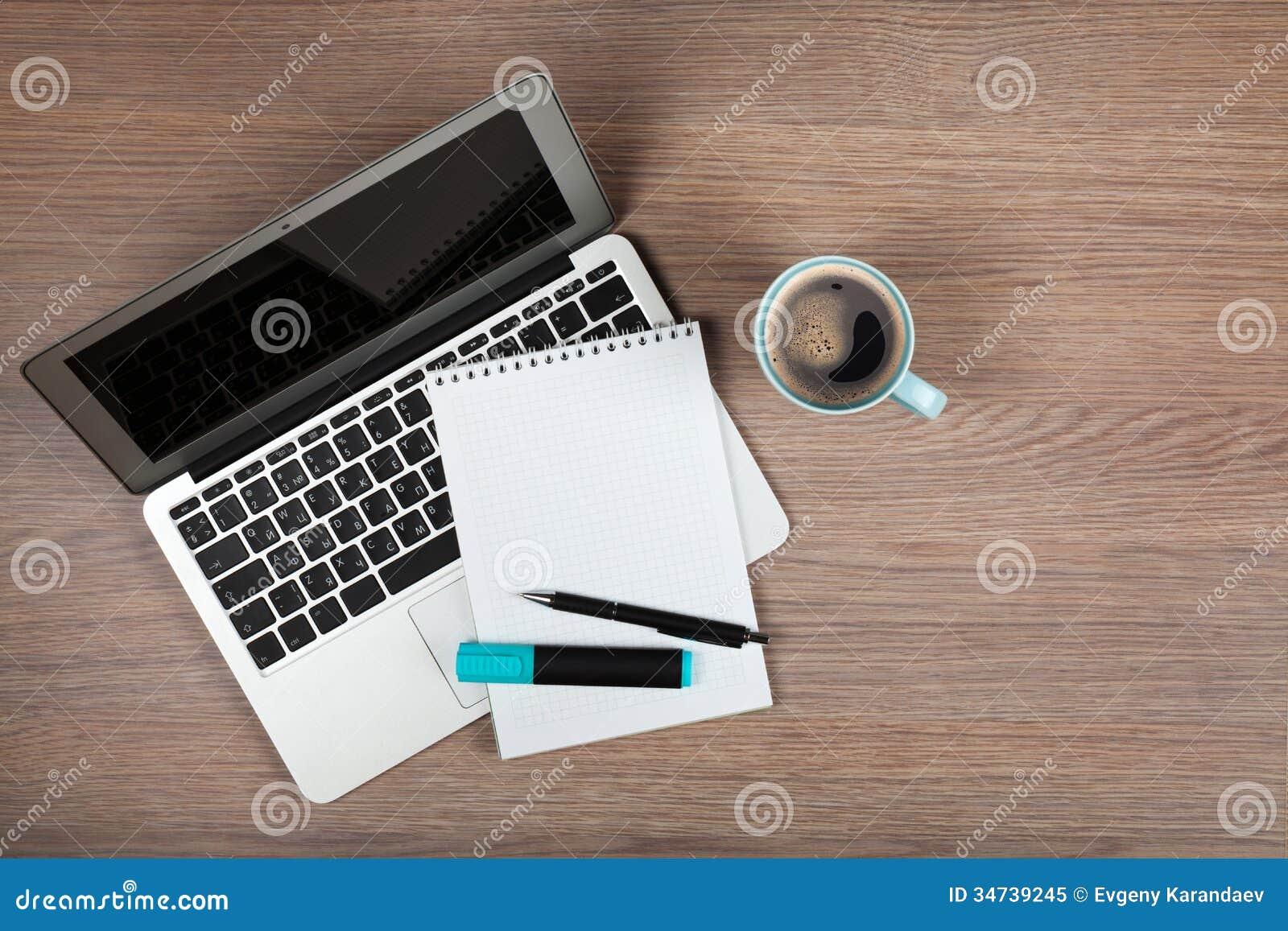 Bloco de notas vazio sobre o copo do portátil e de café