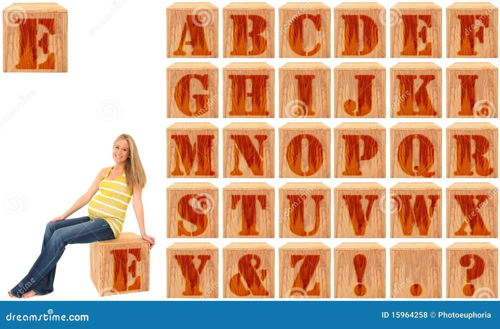 Blocos gravados madeira do alfabeto com mulher gravida