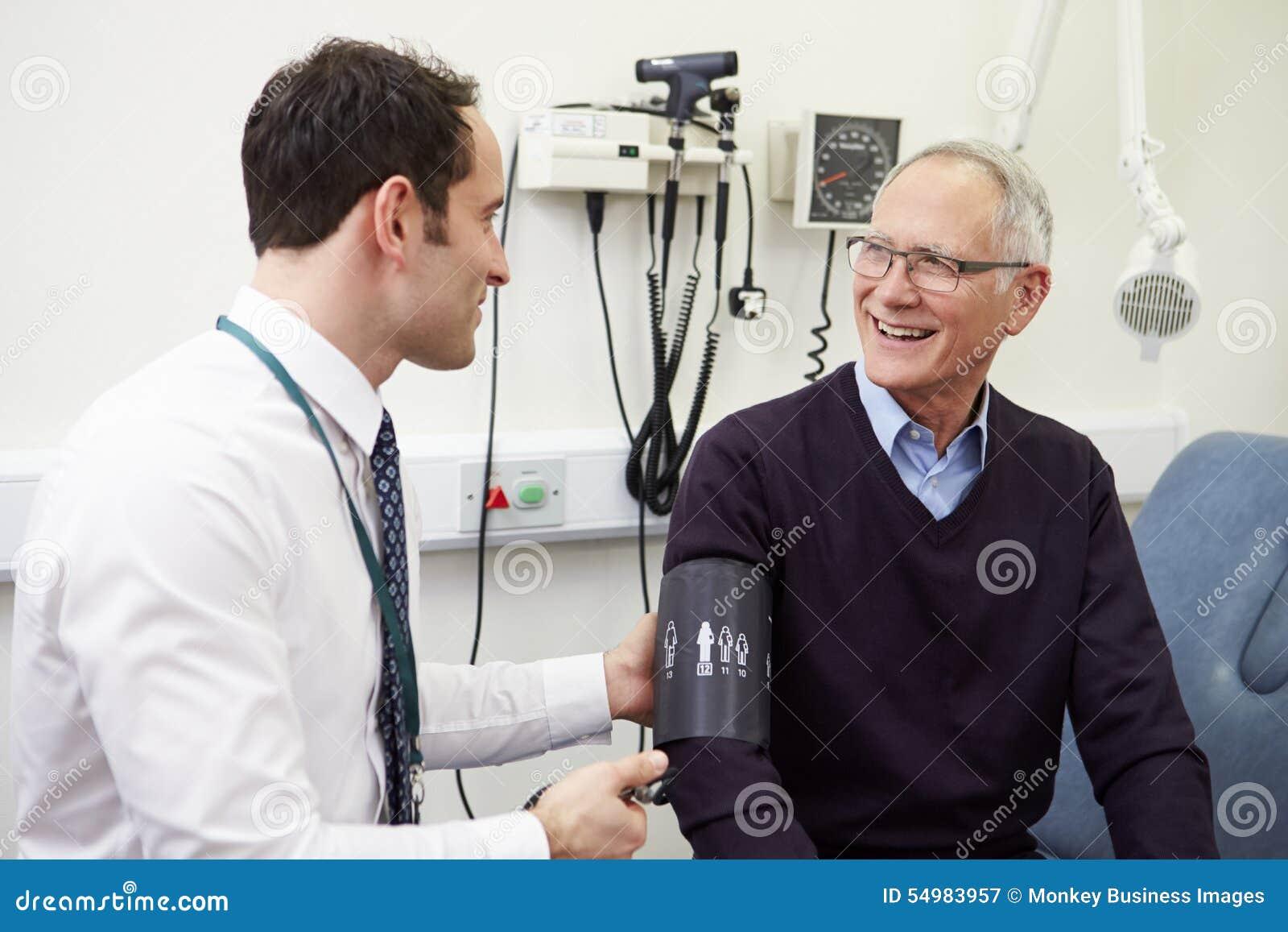 Blodtryck för doktor Taking Senior Patients i sjukhus
