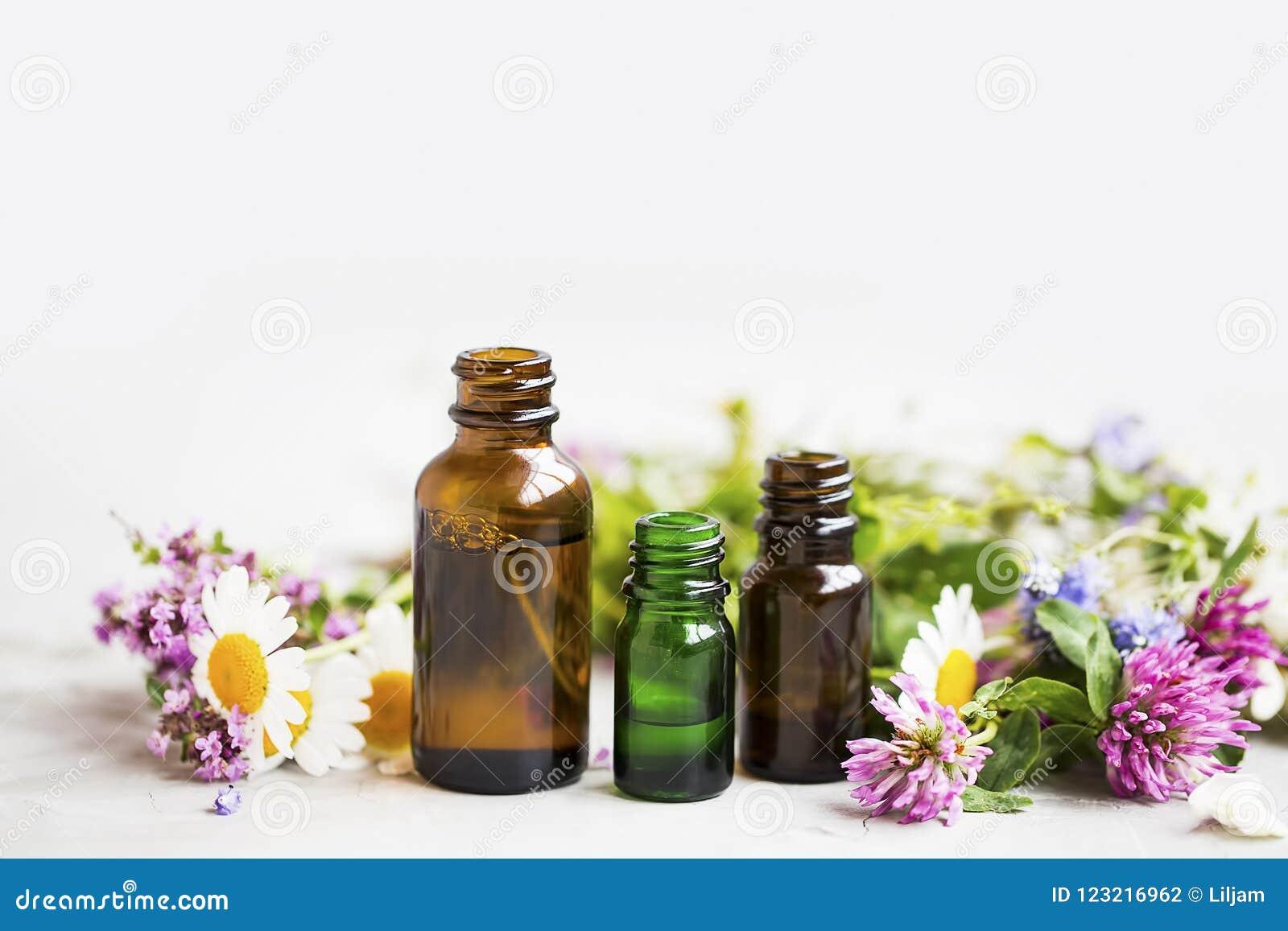 Bloemen en kruidenetherische olieflessen, natuurlijke aromatherapy wi