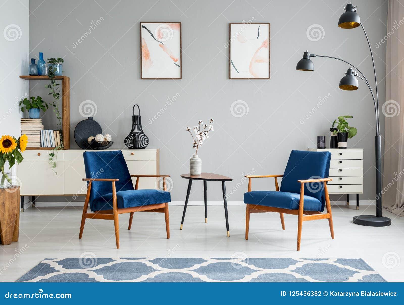 Bloemen op houten lijst tussen blauwe leunstoelen in woonkamerbinnenland met affiches Echte foto