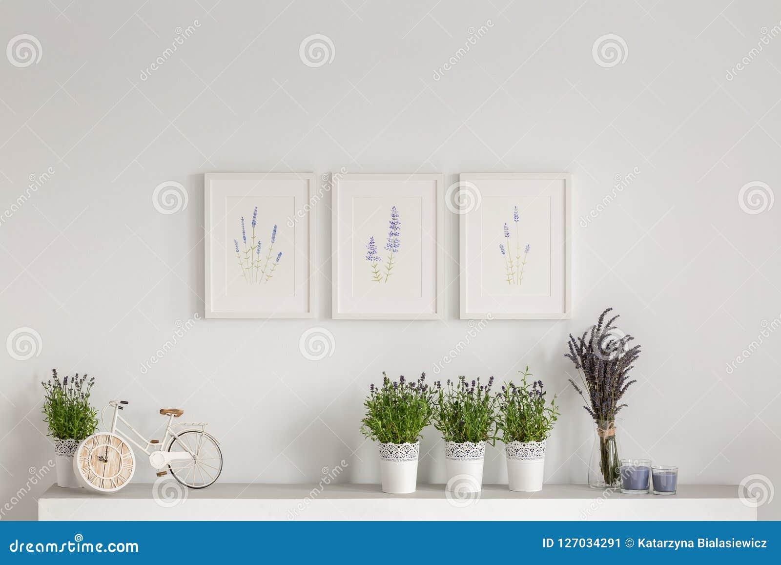 Bloemen op kast tegen witte muur met affiches in minimaal woonkamerbinnenland Echte foto