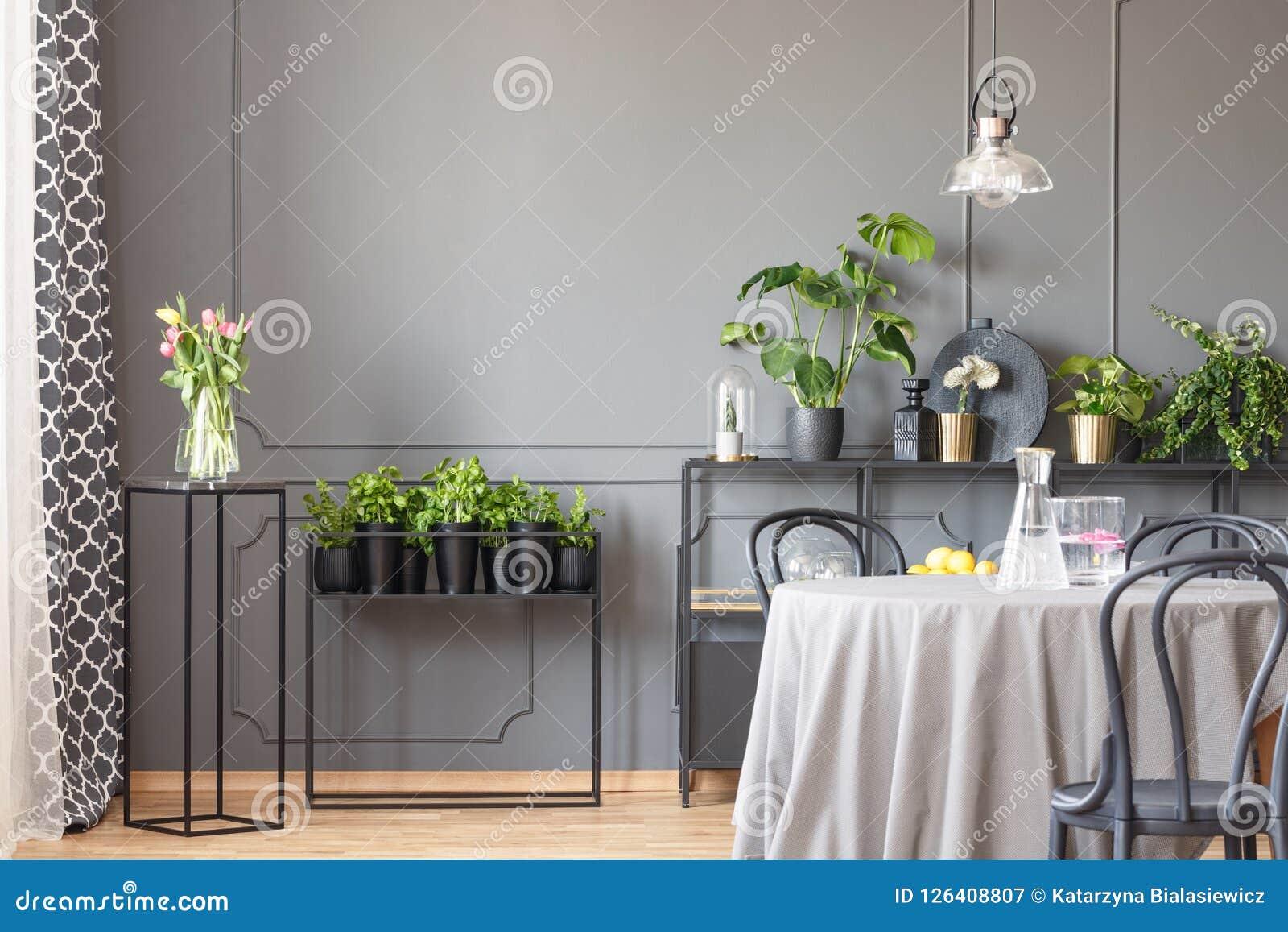 Bloemen op zwarte lijst naast installaties in grijze eetkamerinteri