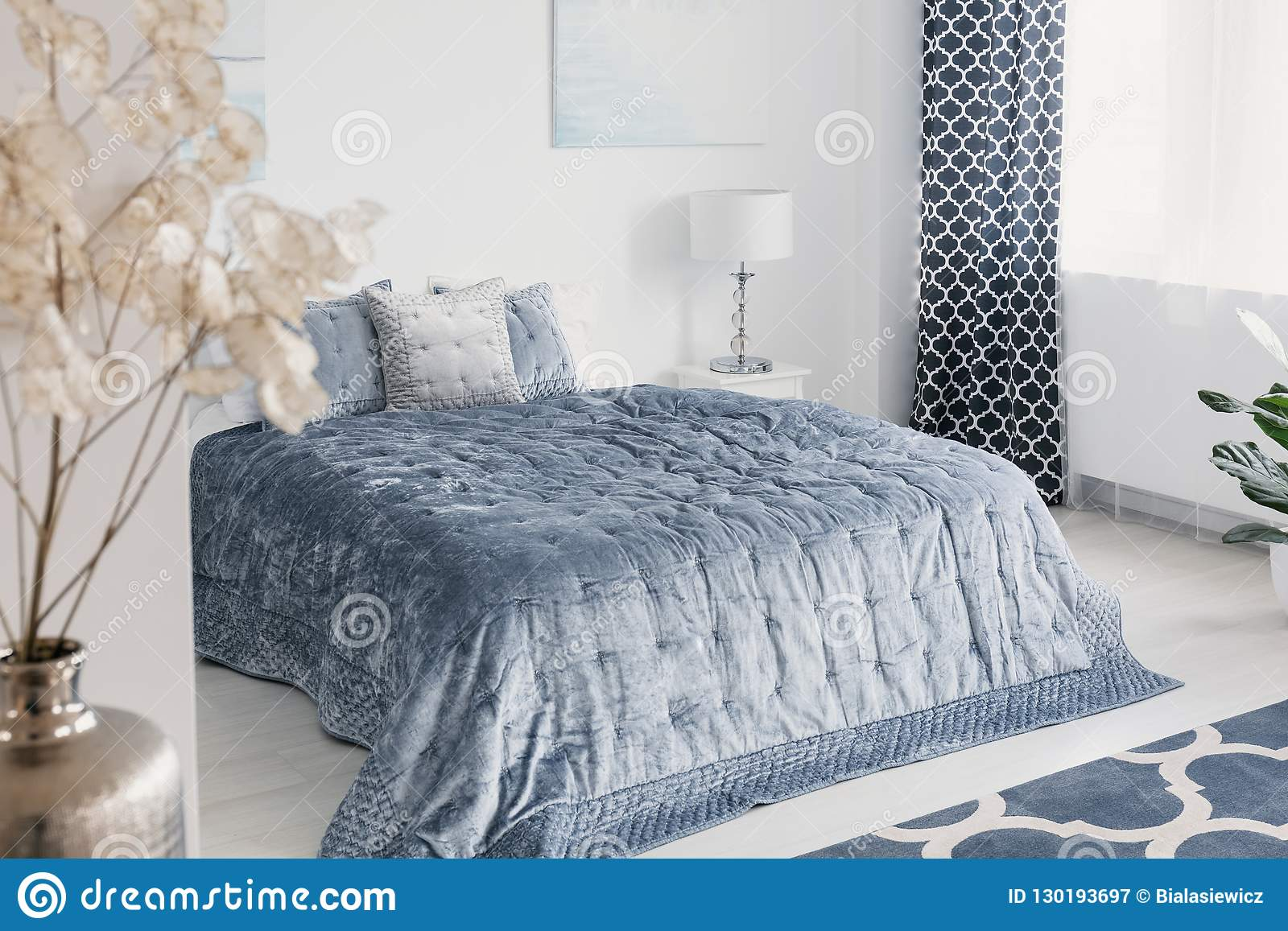 Bloemen in wit elegant slaapkamerbinnenland met blauwe bladen op bed naast lamp en gordijn Echte foto