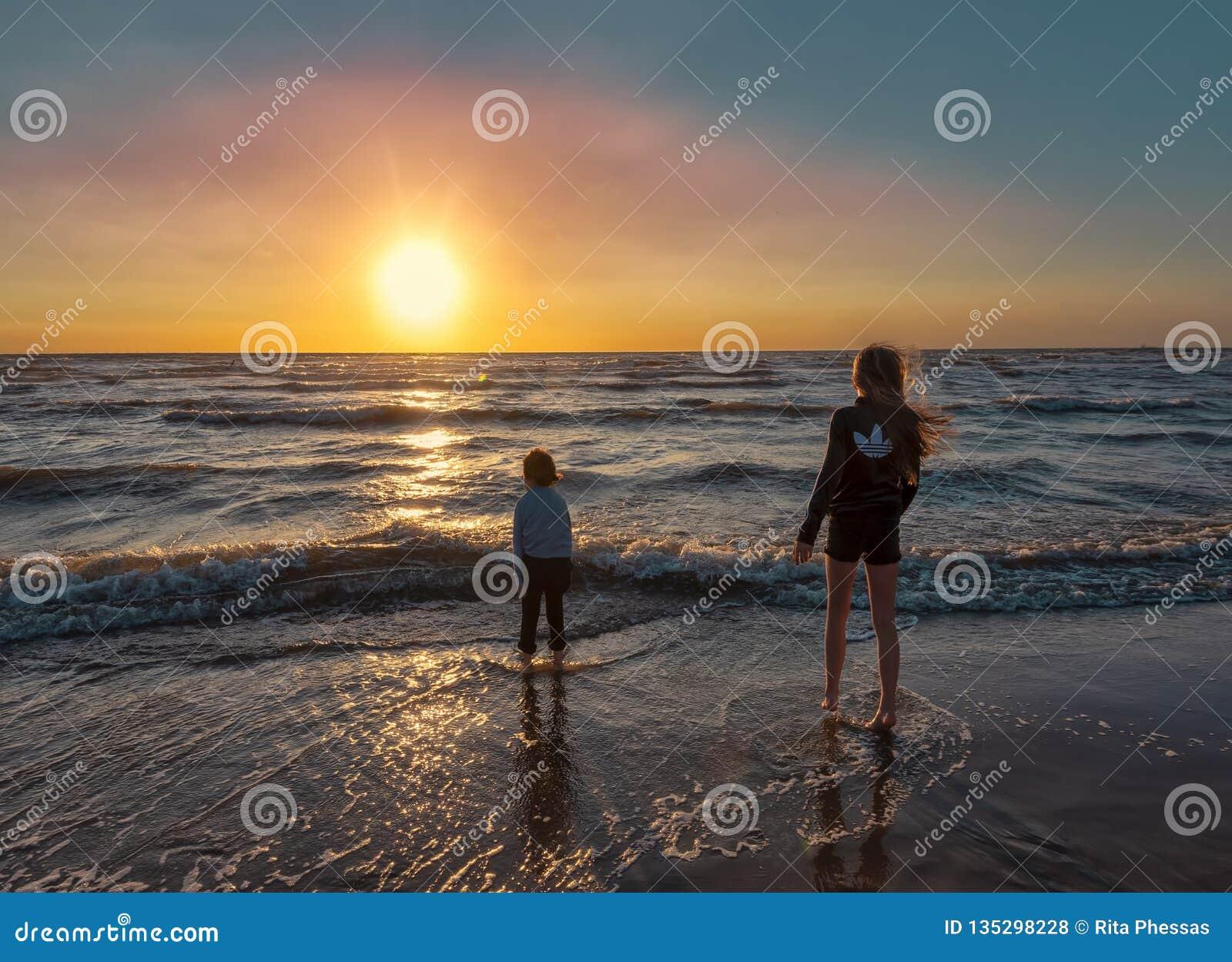 Bloemendaal holandie, 8-8-2018 Chłopiec i dziewczyna bawić się przy plażą z ich ciekami w falach przypływ, podczas gdy t