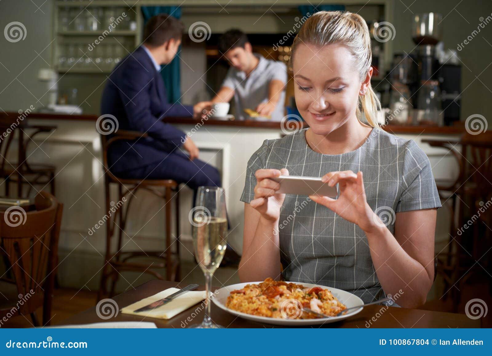 Blogger do alimento que toma a imagem da refeição do restaurante no telefone celular