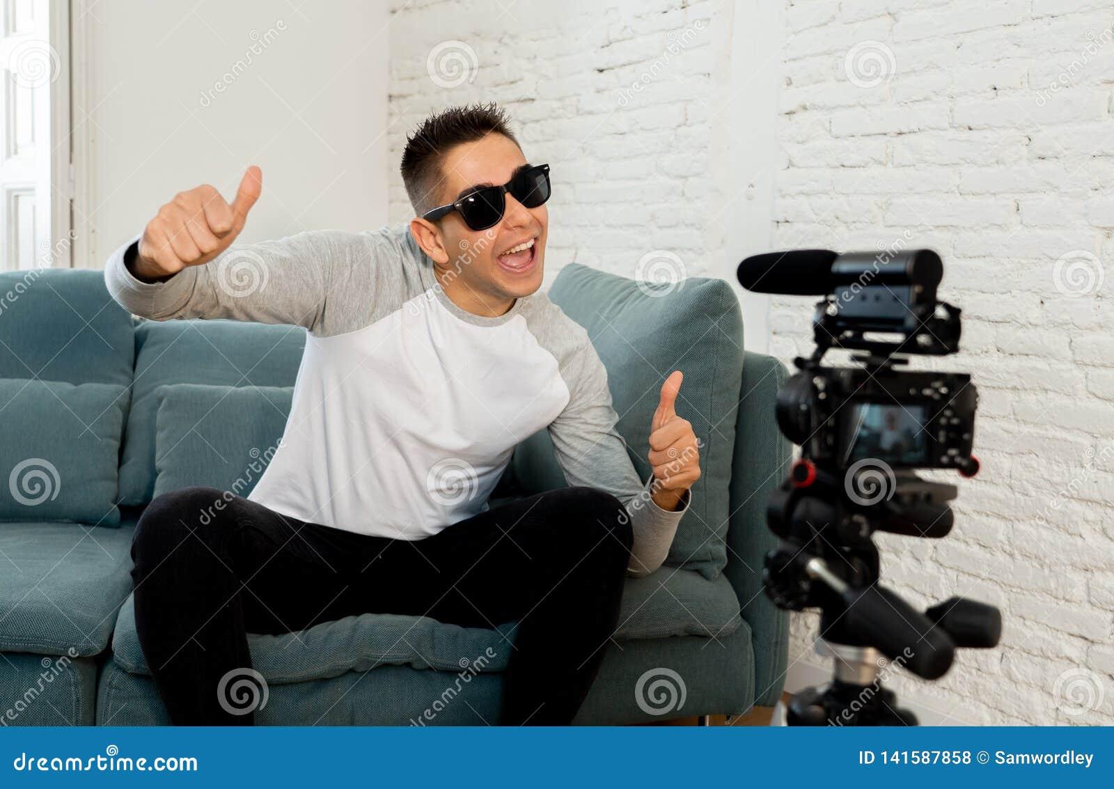 Blogger do homem novo que grava um vídeo na fluência na câmera para os seguidores no Internet