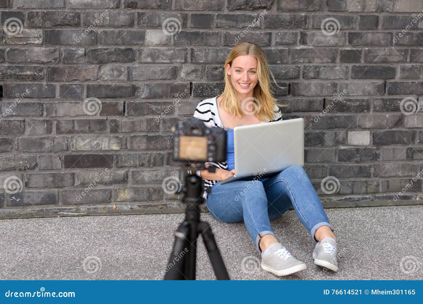 Blogger féminin blond mignon avec la vidéo d enregistrement d ordinateur portable