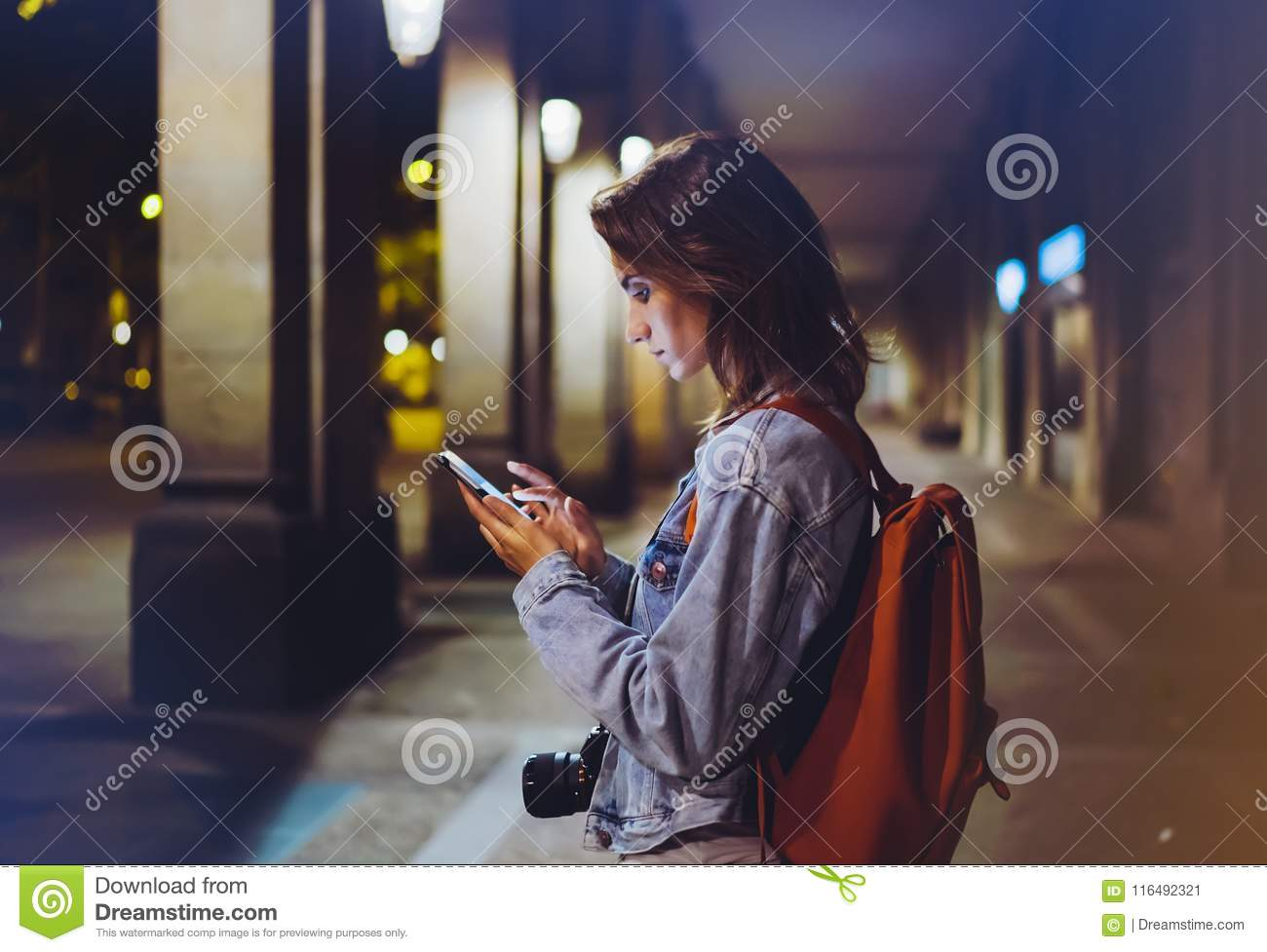 Blogger hipster using in hands gadget mobile phone, woman with backpack pointing finger on blank screen smartphone on background b