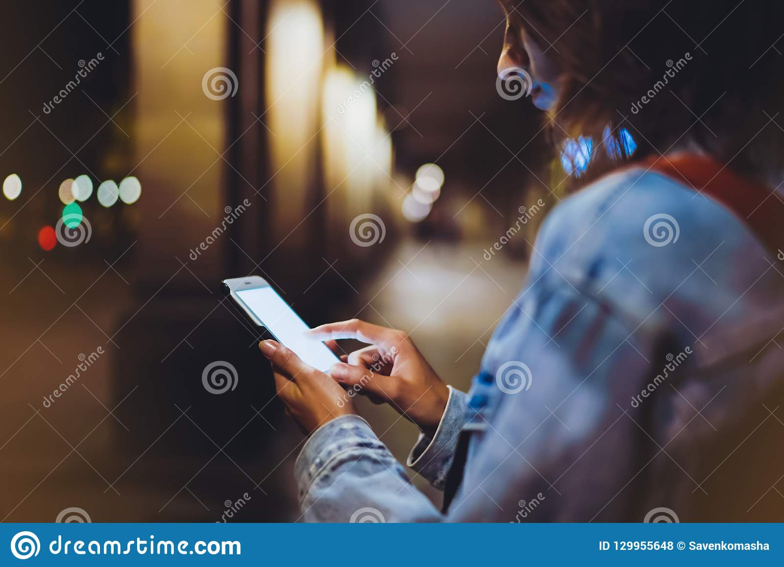 Blogger hipster using in hands gadget mobile phone, woman with backpack pointing finger on blank screen smartphone on background