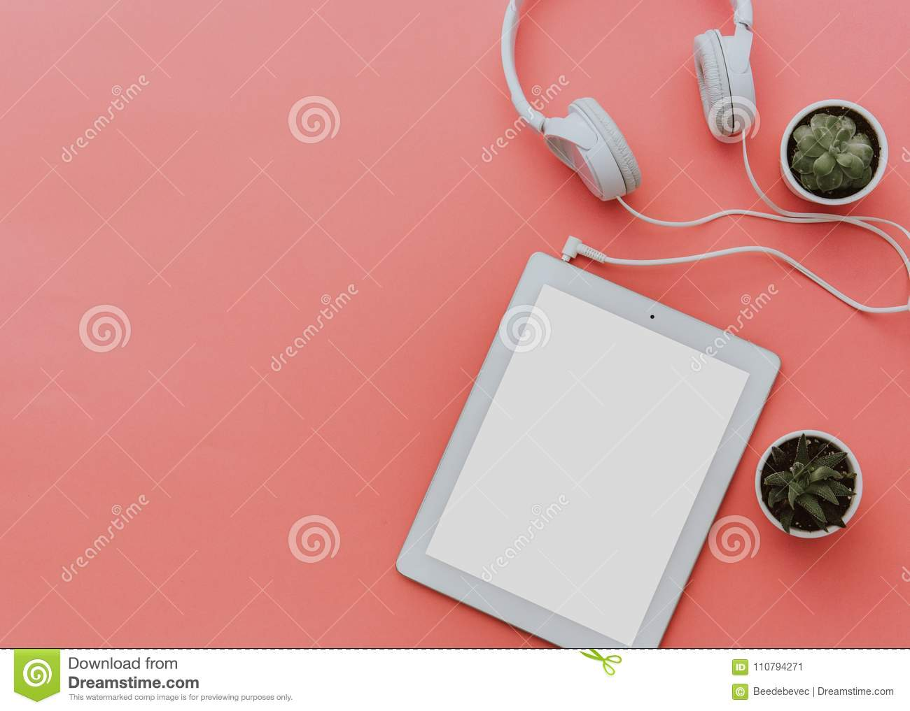 Blogger workspace with tablet and headphones on pastel background. Mock up, Flat lay, top view, minimalistic styled home office