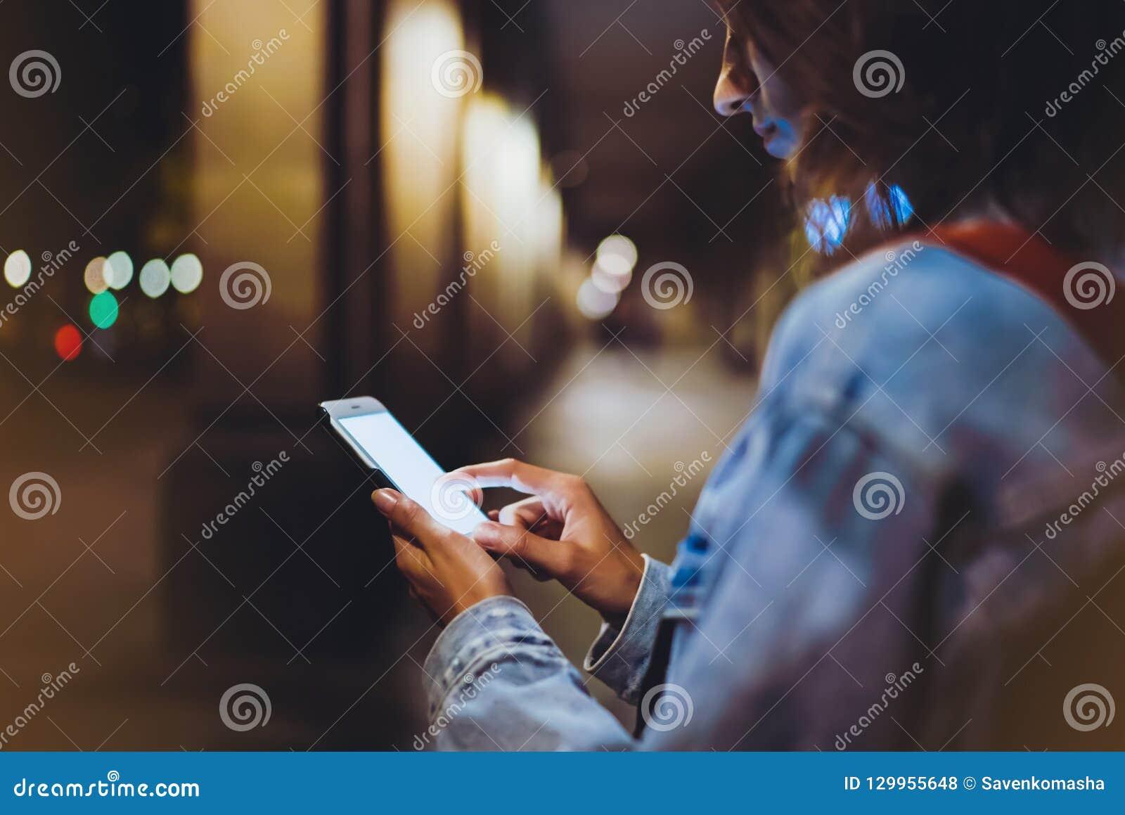 Bloggerhippie, der im Handgeräthandy, Frau mit Rucksack Finger auf Smartphone des leeren Bildschirms auf Hintergrund zeigend verw
