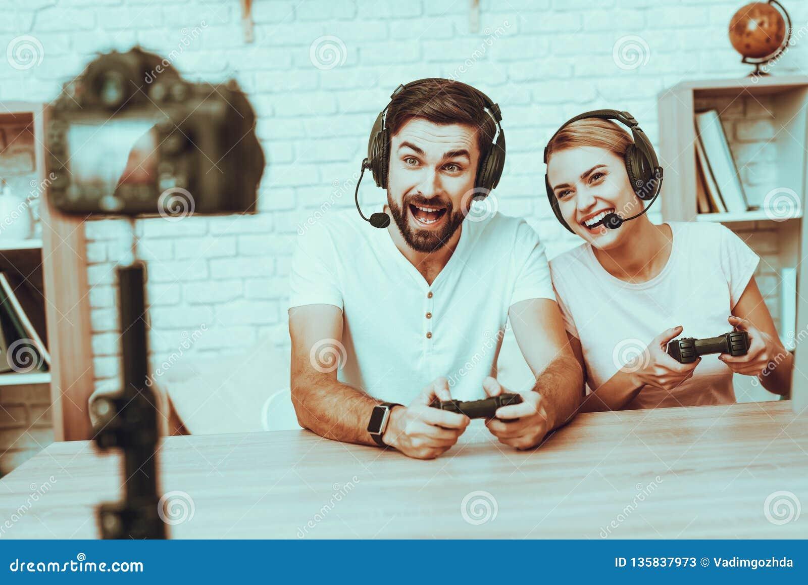 Bloggers que jogam um jogo de vídeo no console
