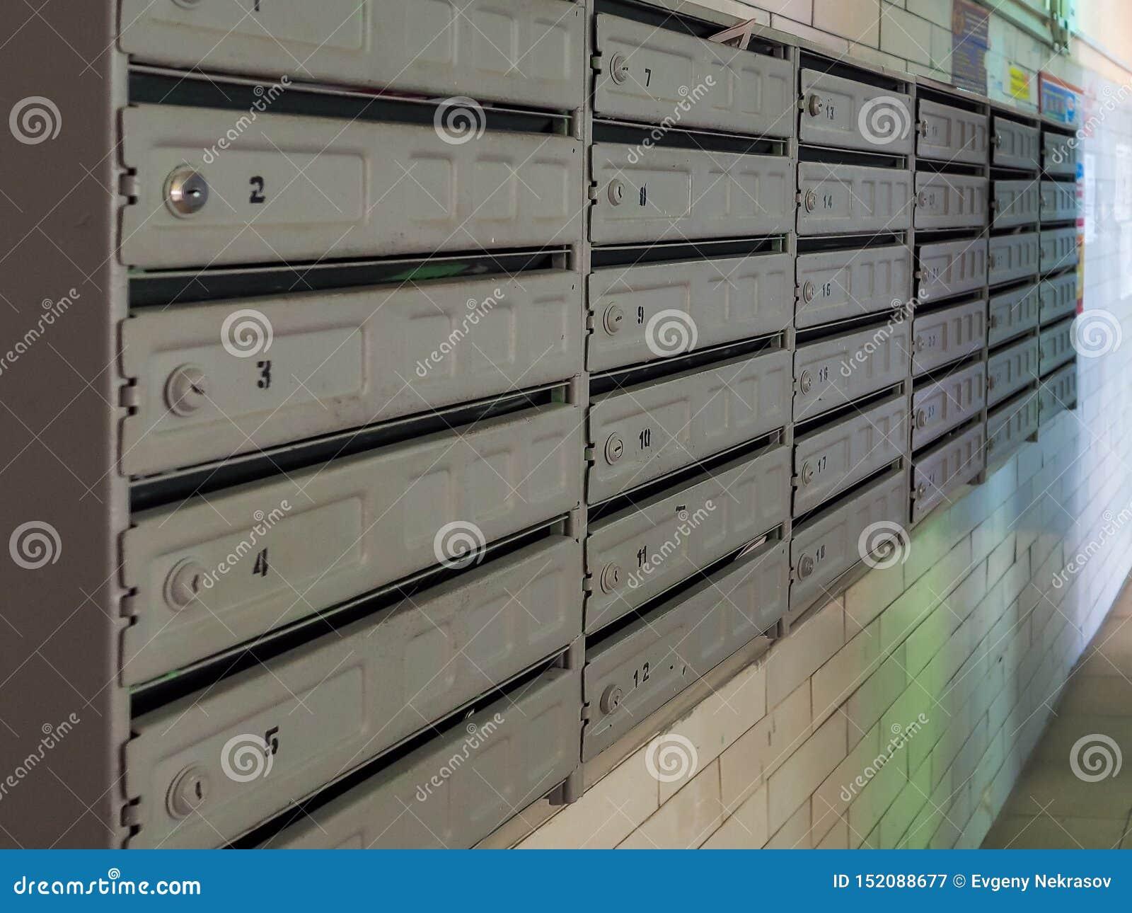 Blokowe skrzynki pocztowe w wejściu stary budynek mieszkaniowy W oczekiwaniu na kwit korespondencja