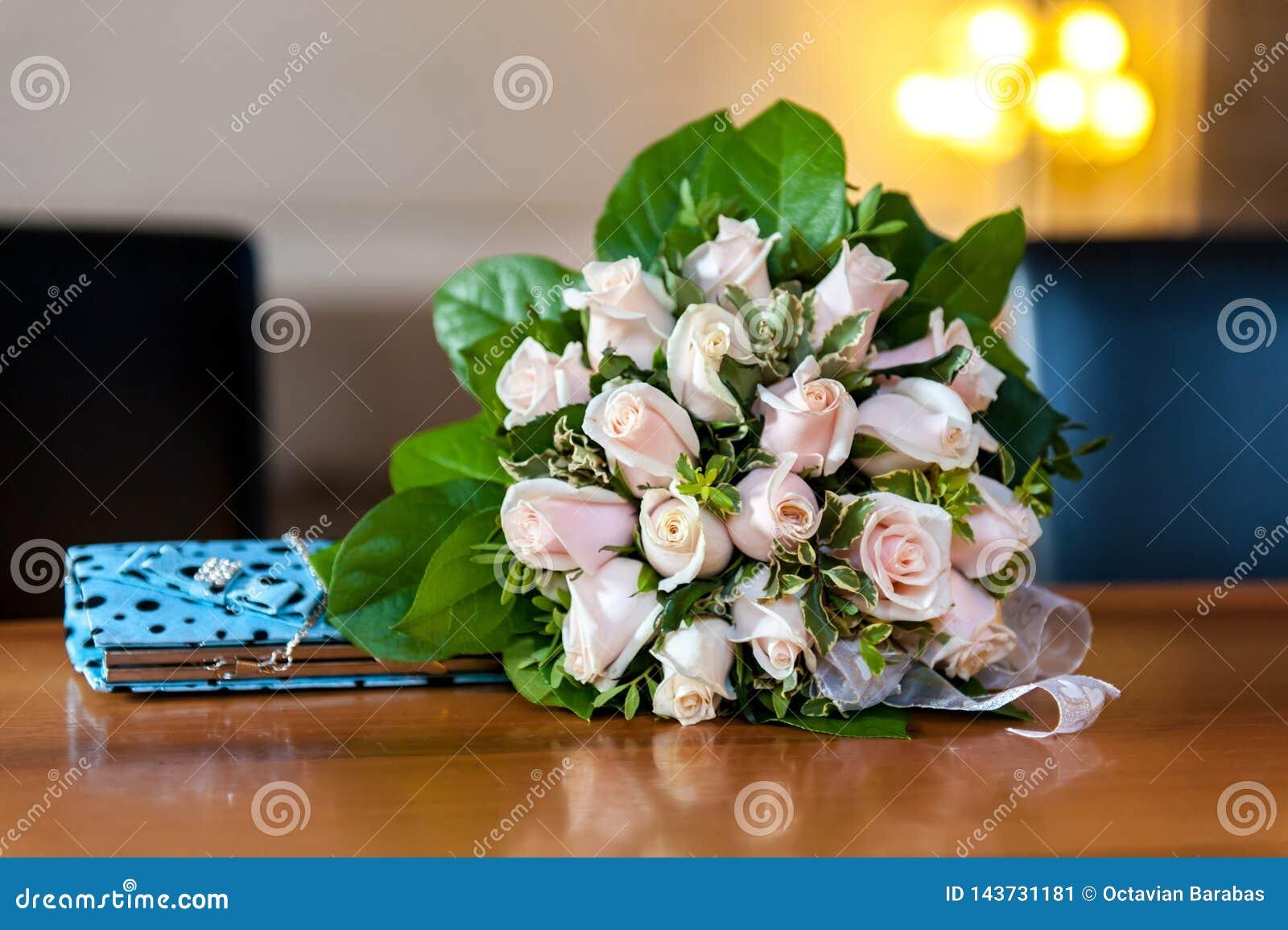 Blommabukett och turkoshandväska på trätabellen