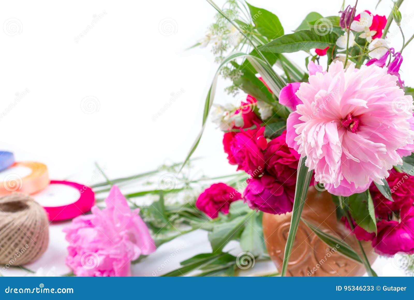 Blommaordning med en härlig bukett av rosa pionblommor, blåklinter och röda rosor på en vit bakgrund med utrymme för