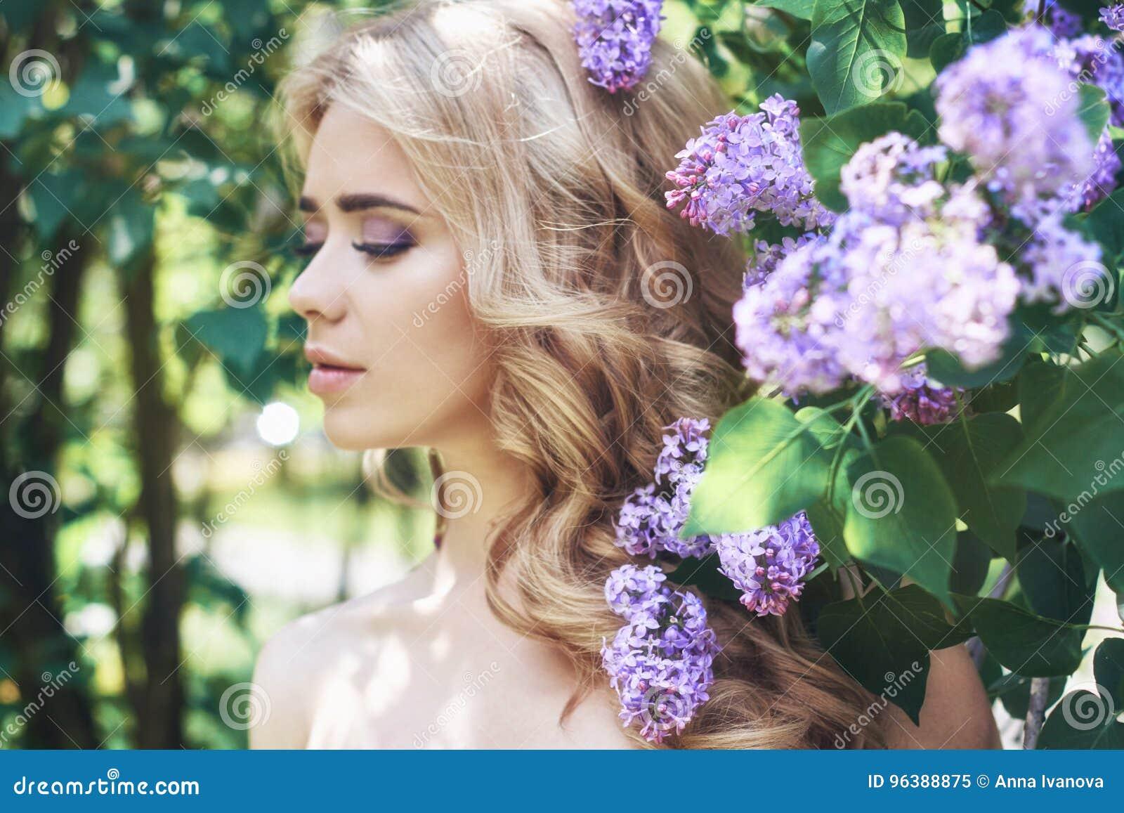 Blommar den härliga unga kvinnan för utomhus- mode som omges av lilan, sommar Lila buske för vårblomning Stående av en blond flic