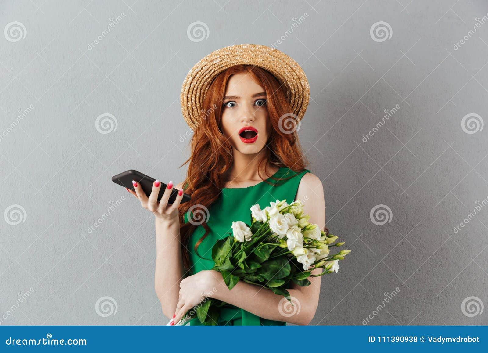 Blommar den unga chockade kvinnan för rödhåriga mannen att prata vid telefonen