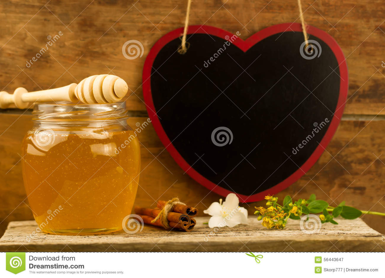 Blommar ny honung för den Glass kruset med drizzler, kanel, på träbakgrund