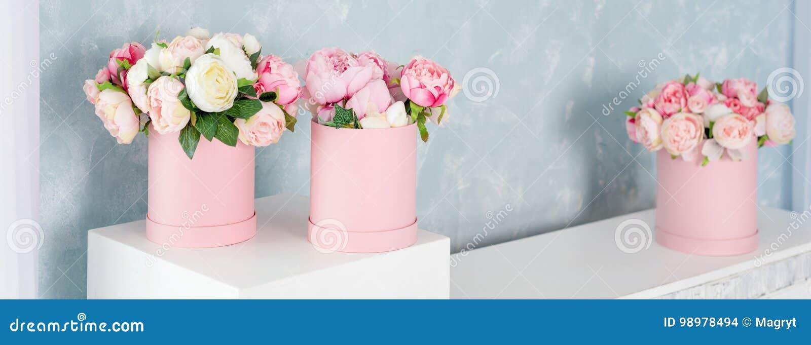 Blommor i runda lyxgåvaaskar Bukett av rosa och vita pioner i pappers- ask Modell av hattasken av blommor