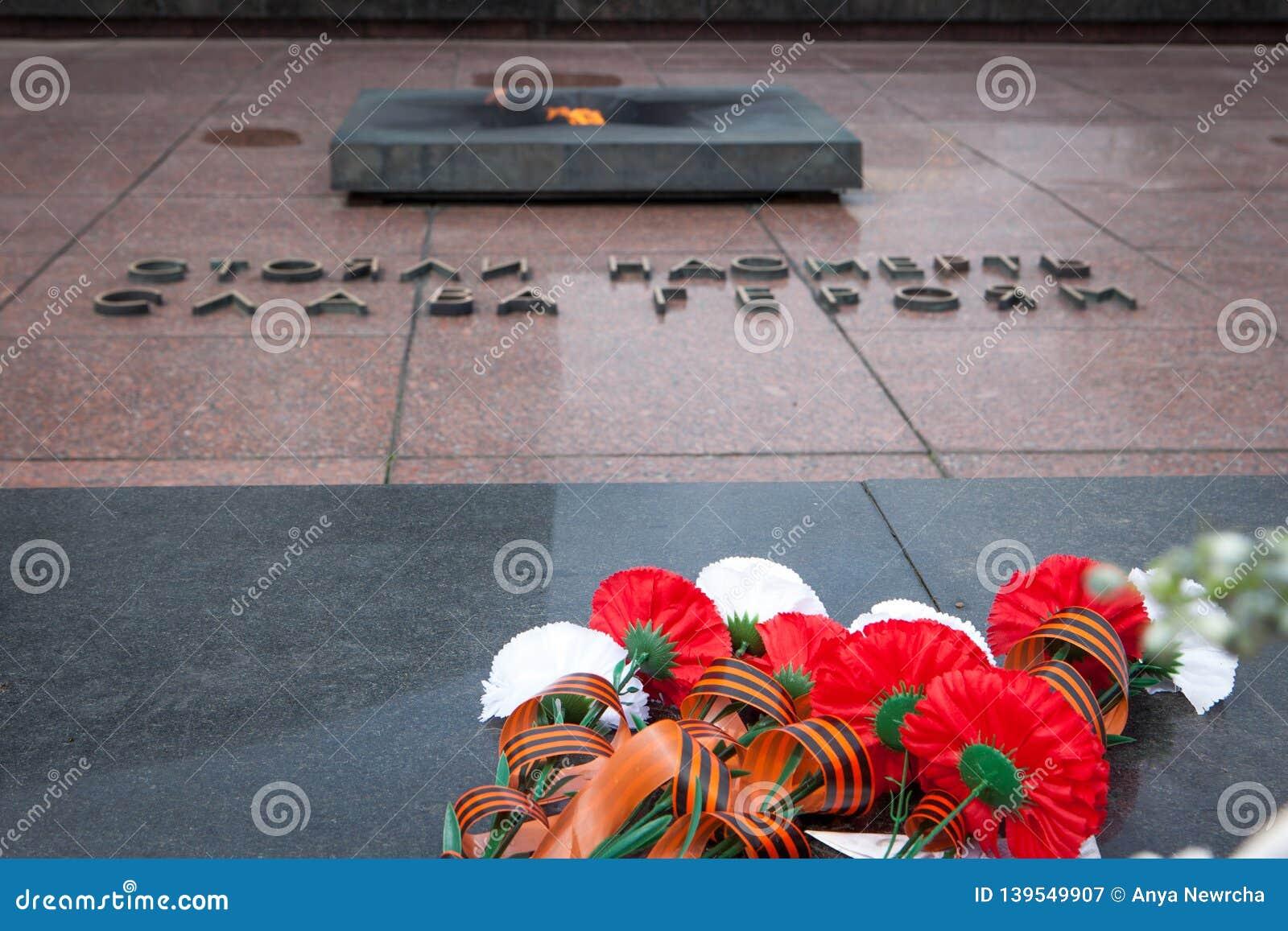 Blommor på gravstenen av den okända soldaten och evigt ljus
